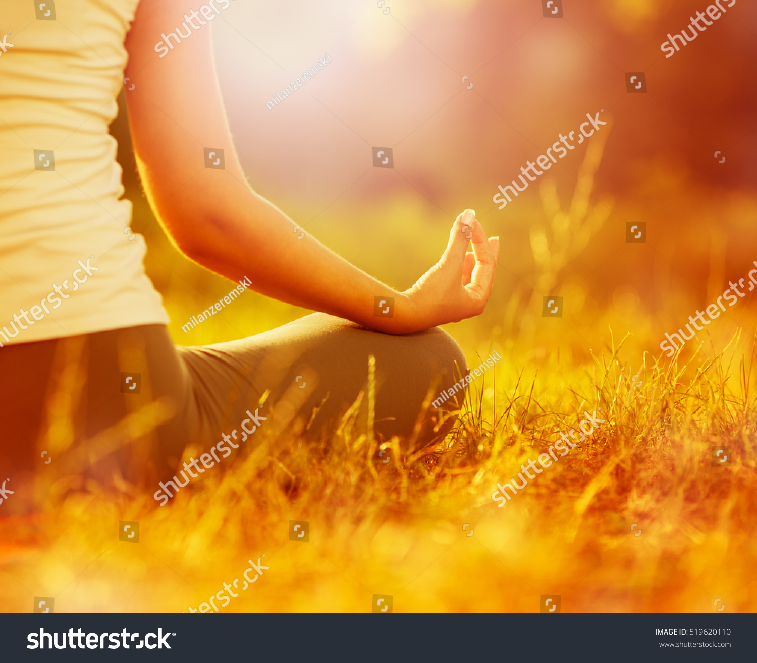 Young woman practicing morning meditation in nature at the park Health lifestyle concept