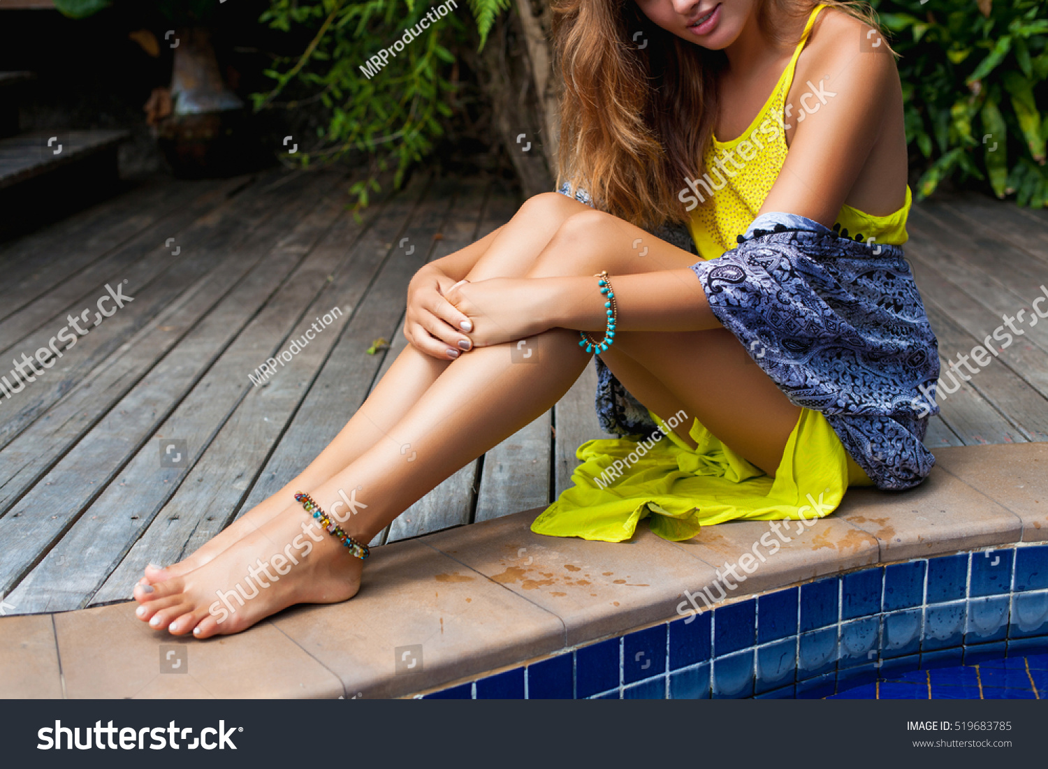 young beautiful woman sitting at pool in yellow boho dress, summer trend  fashion, sexy