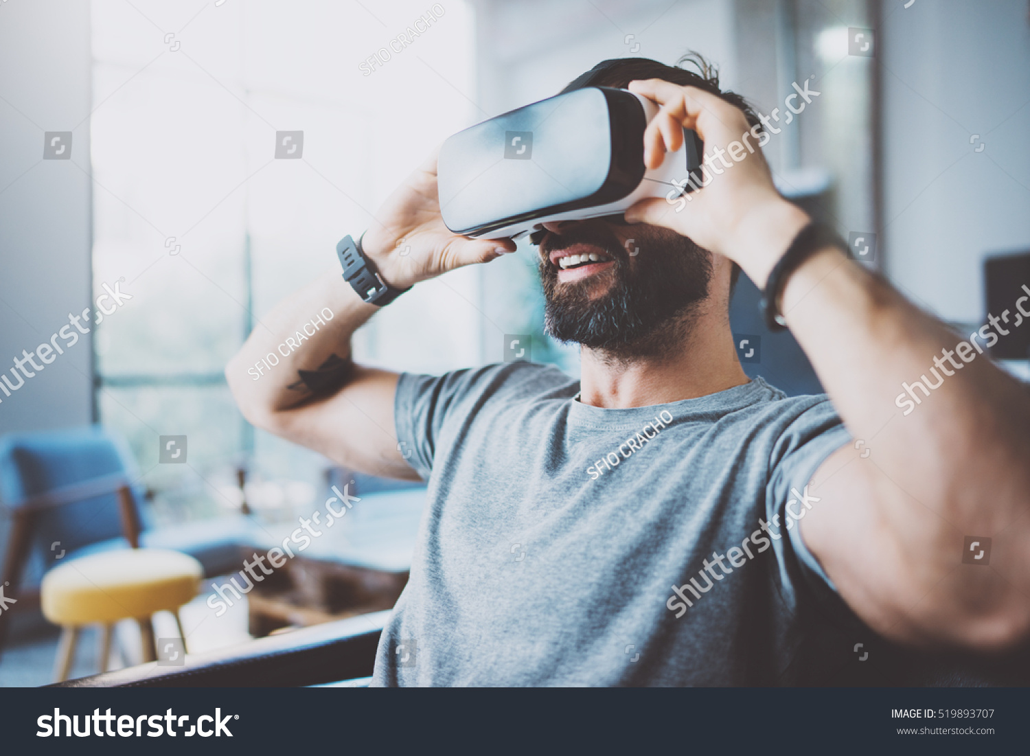 Bearded man wearing virtual reality goggles in modern coworking studio. Smartphone using with VR headset. Horizontal, blurred