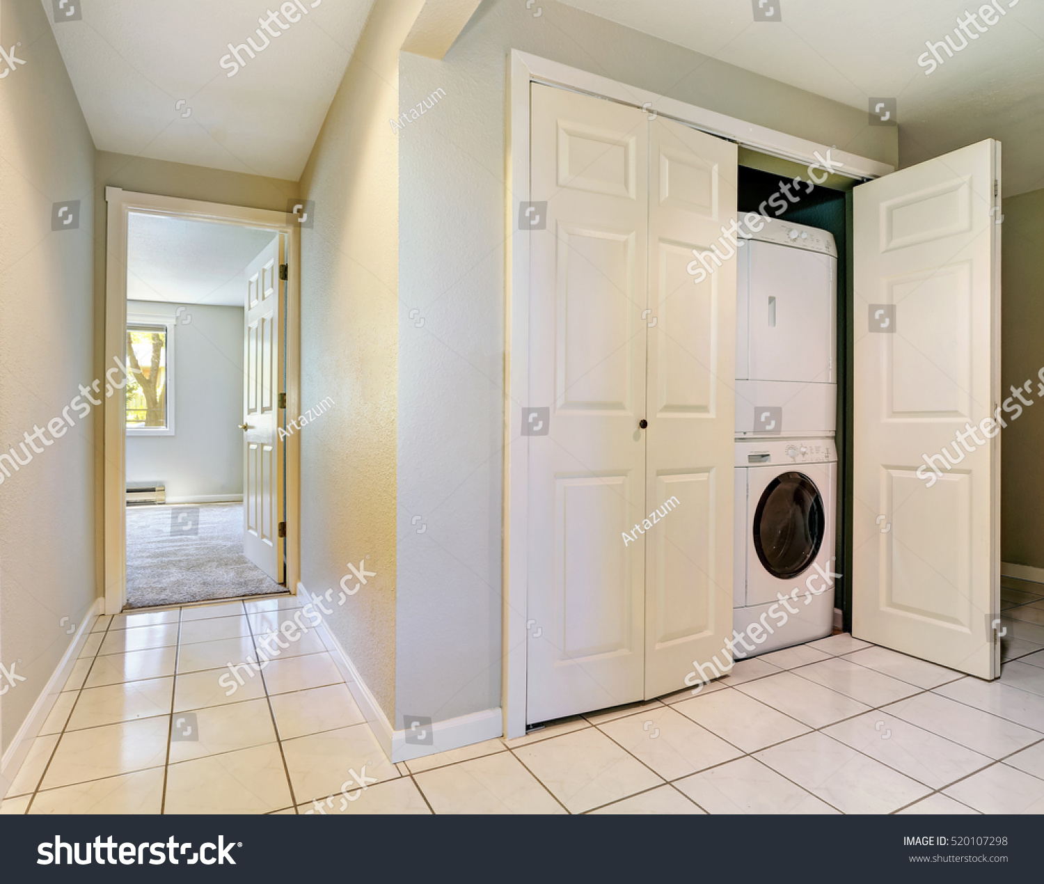 Hallway Interior With Tile Floor And Built In Laundry Appliances