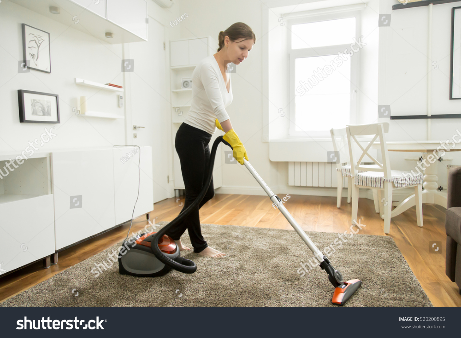 Woman casual wear vacuum cleaning carpet stock photo for Modern cleaning concept