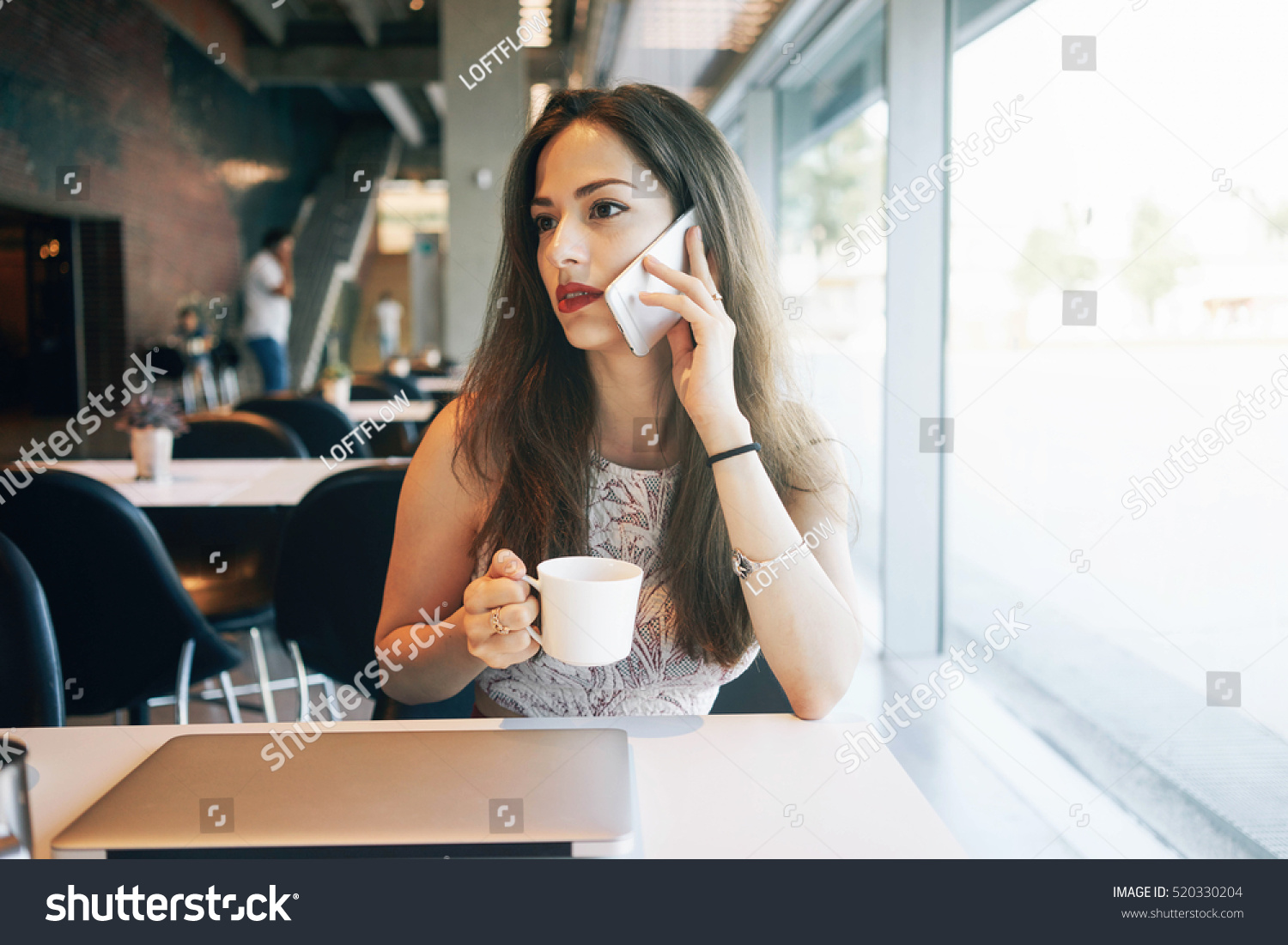 A caucasian female freelancer is talking on a phone while sitting in a cafe with a portable computer on a table Young attractive business woman is making a business call during the lunch break