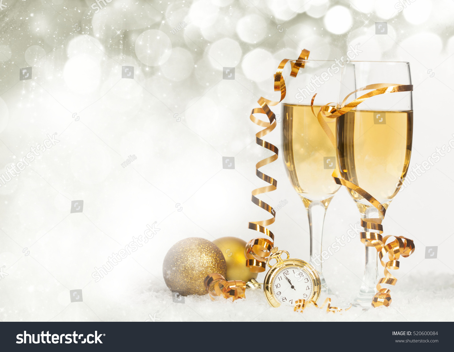 glasses with champagne and golden christmas balls against holiday lights new year background