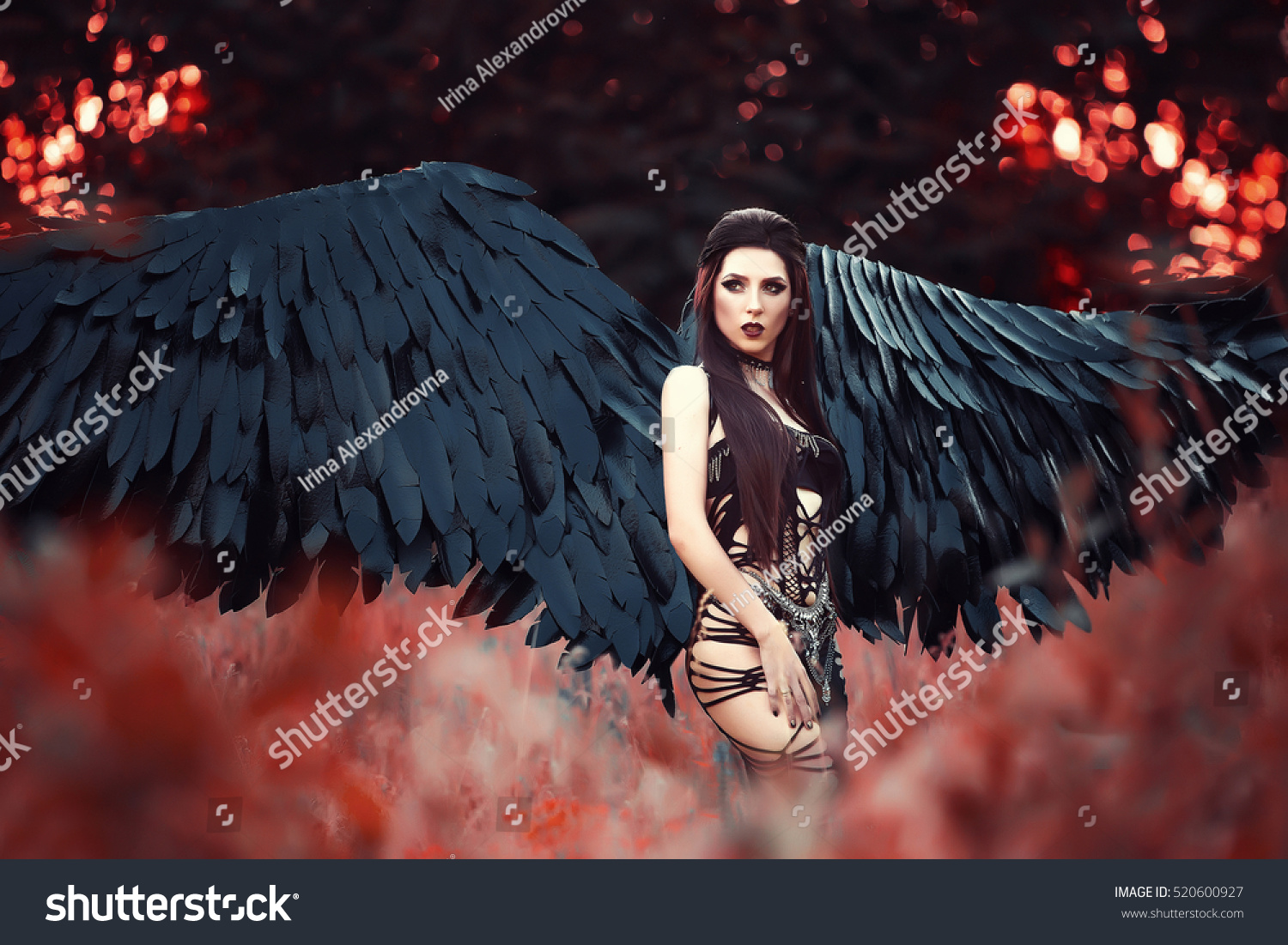 Beautiful sexy girl-demon with spreading black wings in a tempting long