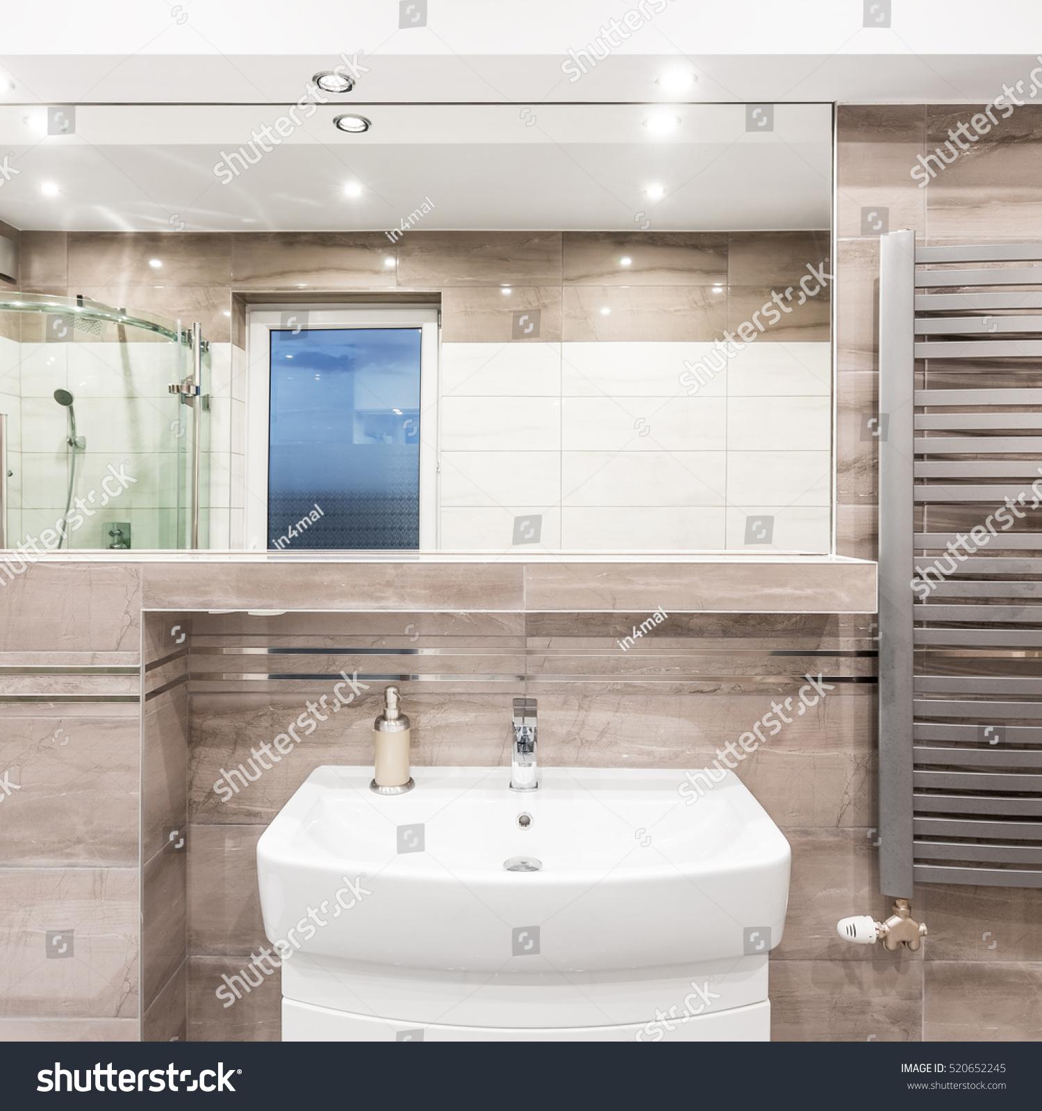 Modern bathroom interior with brown and beige tiles, large bathtub ...
