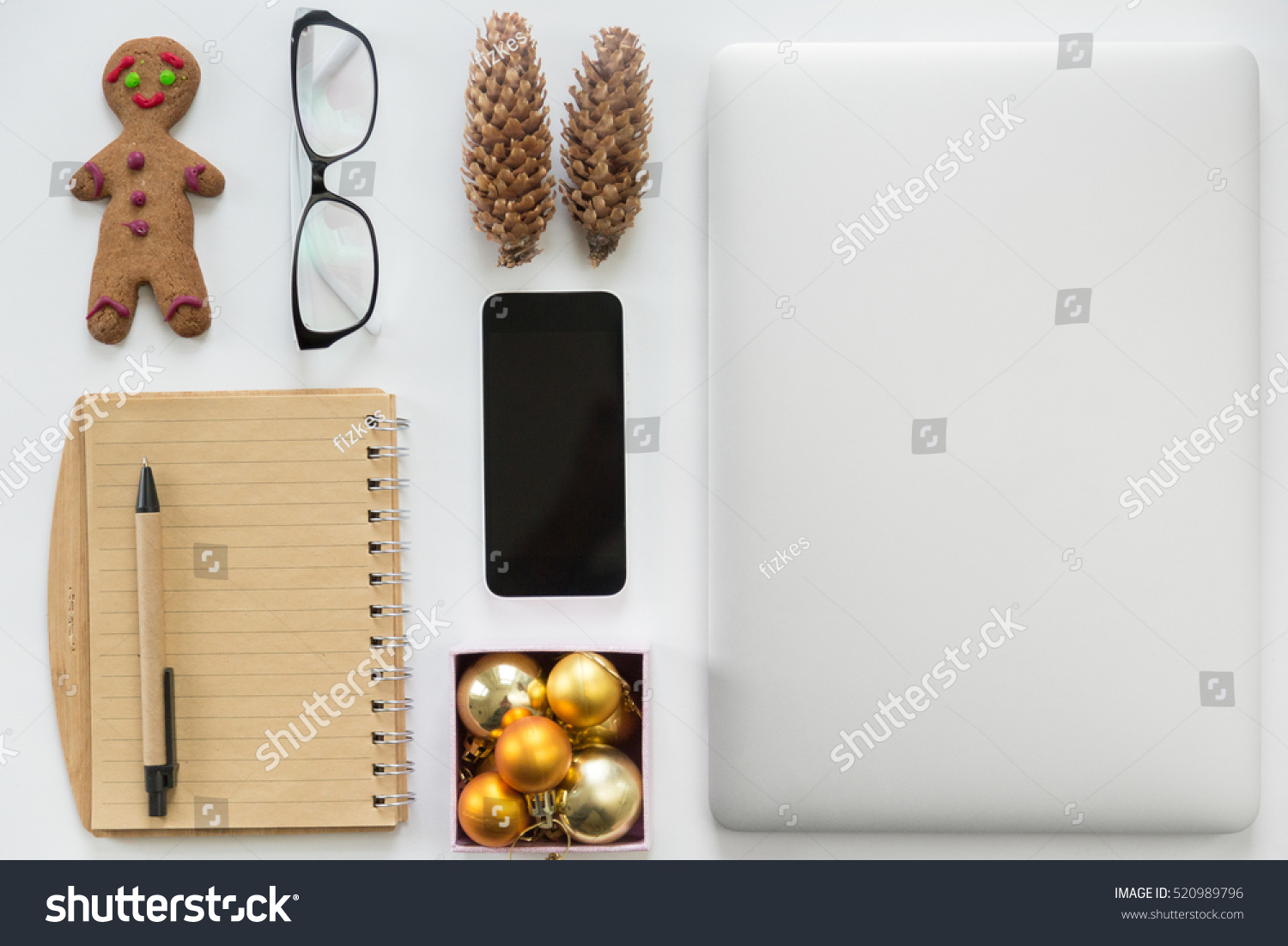 laptop closed mobile phone office supply and christmas decoration on a white office desk - Office Supply Christmas Decorations
