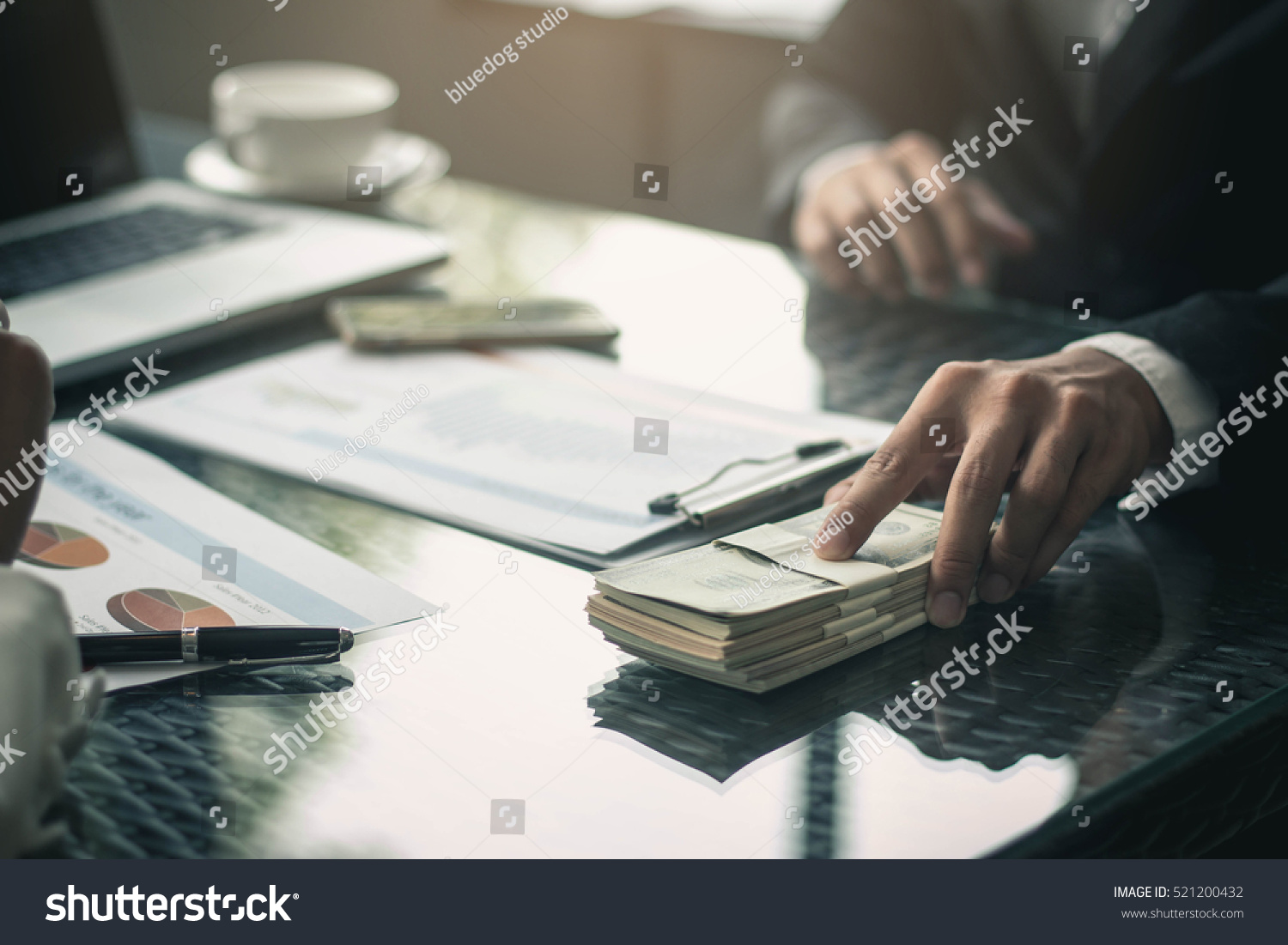 Man offering batch of hundred dollar bills. Hands close up. Venality, bribe, corruption concept. Hand giving money - United States Dollars (or USD). Hand receiving money from businessman. #521200432