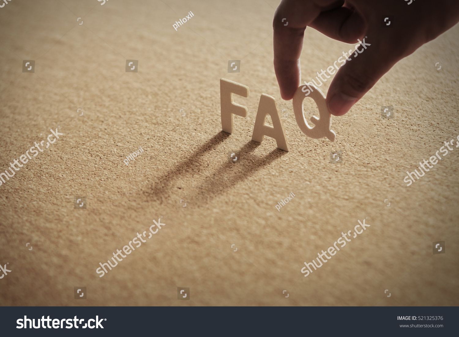 FAQ wood word on compressed board,cork board with human's finger at Q letter