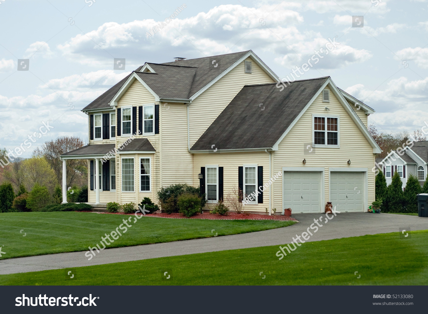 A Modern Colonial Style Residential Suburban Home With A Small Porch And A Two Car Garage Stock