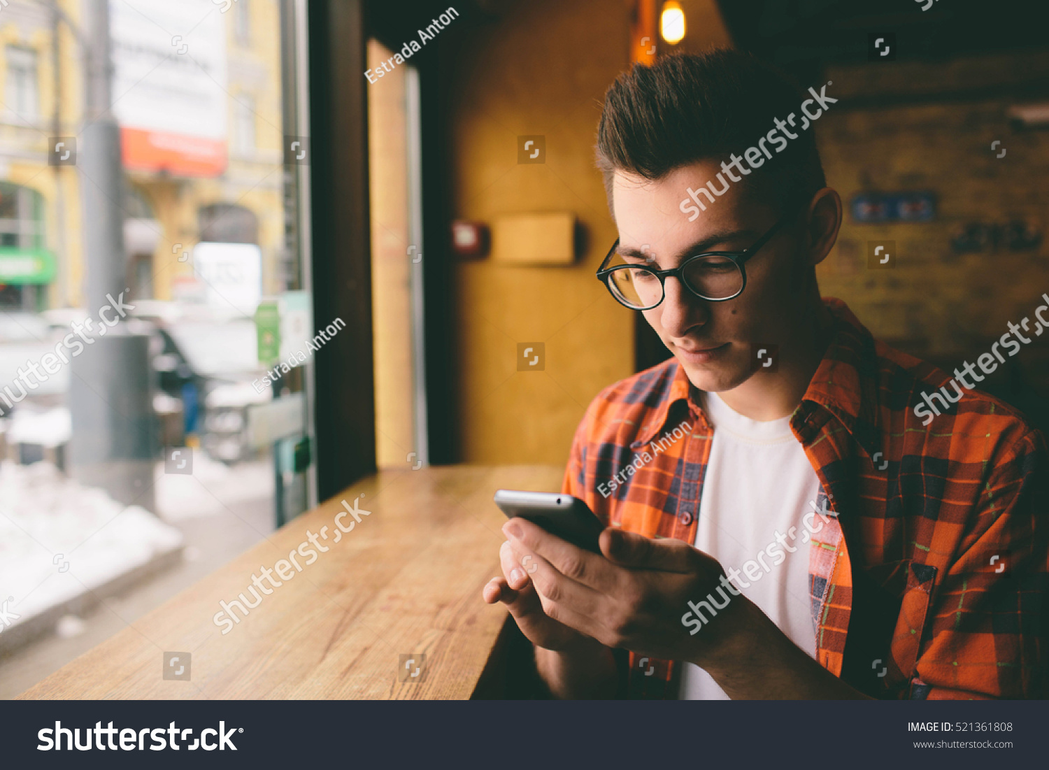 Close up on the hands of a young handsome man using a smartphone tapping the screen technology social network communication concept