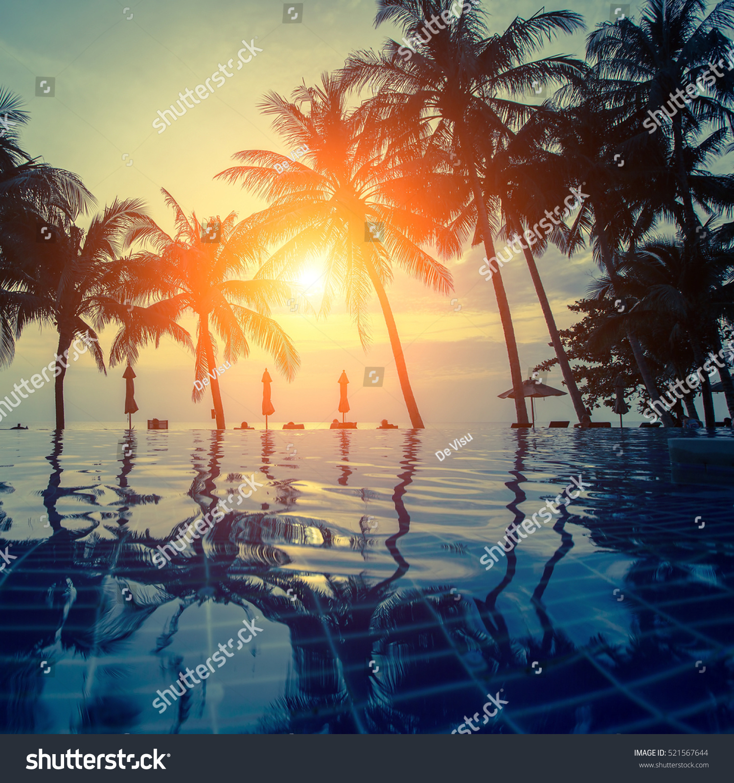 Sunset On Tropical Resort Beach Silhouettes Stock Photo