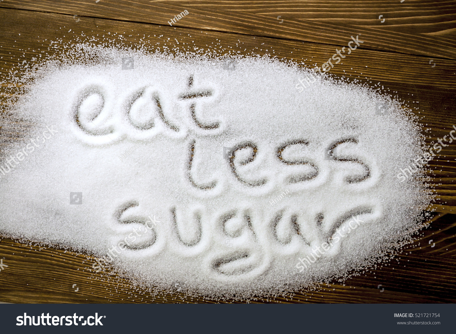 EAT LESS SUGAR written on brown wooden table Health concept