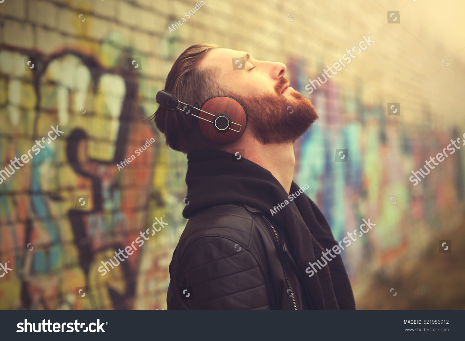 Handsome man in headphones listening to music outdoors #521956912