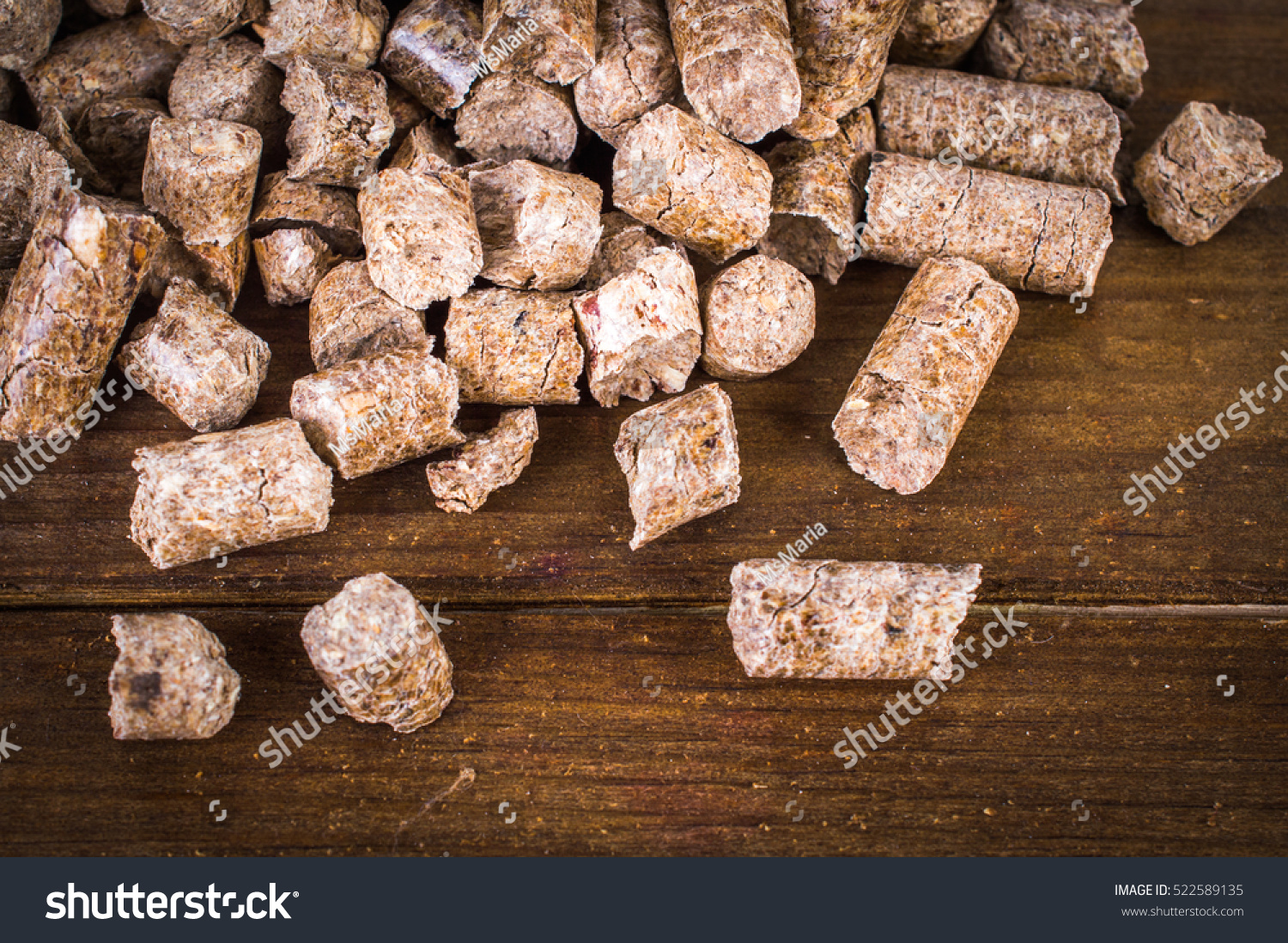 Wood pellets on wooden background stock photo