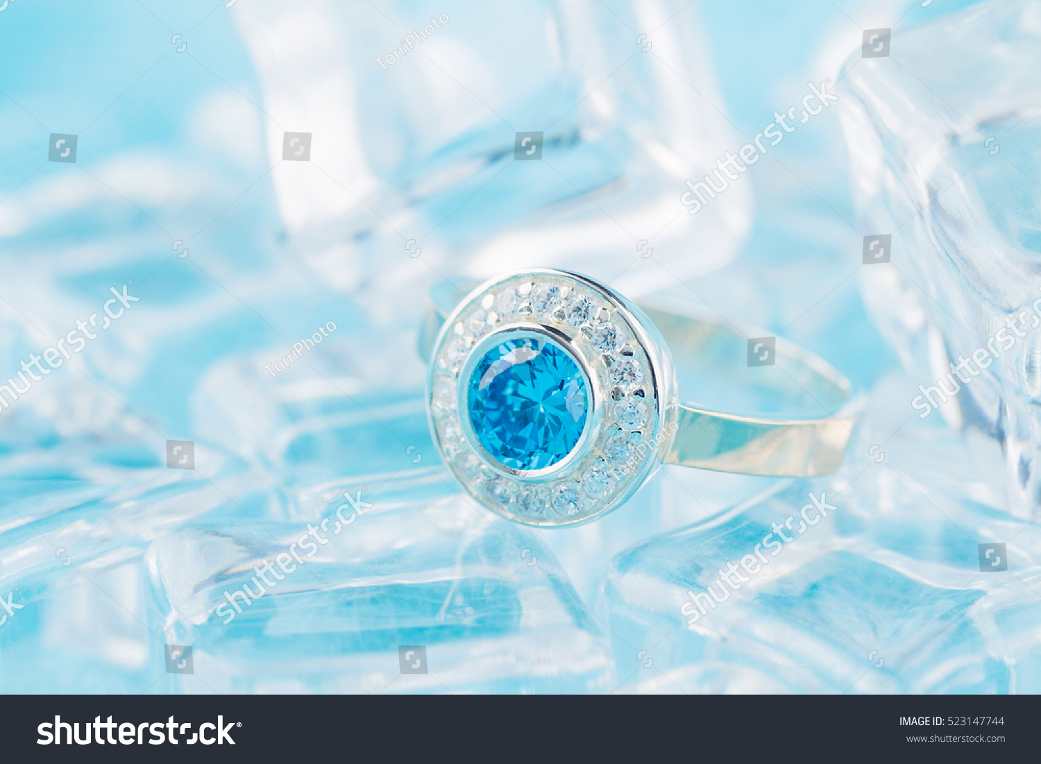 https://www.shutterstock.com/pic-523147744/stock-photo-close-up-silver-ring-with-zircon-and-expensive-blue-gemstone-still-life-on-ice-blue-background.html