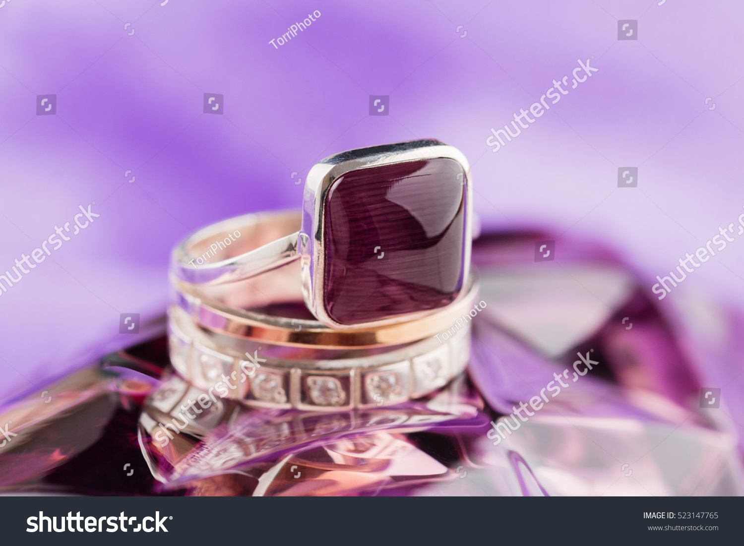 https://www.shutterstock.com/pic-523147765/stock-photo-gold-ring-square-shaped-with-purple-gemstones-on-violet-background.html