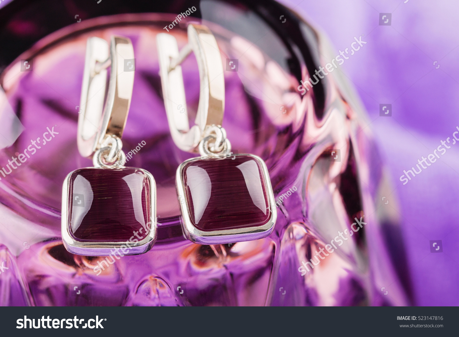 https://www.shutterstock.com/pic-523147816/stock-photo-gold-ring-square-shaped-with-purple-gemstones-on-violet-background.html