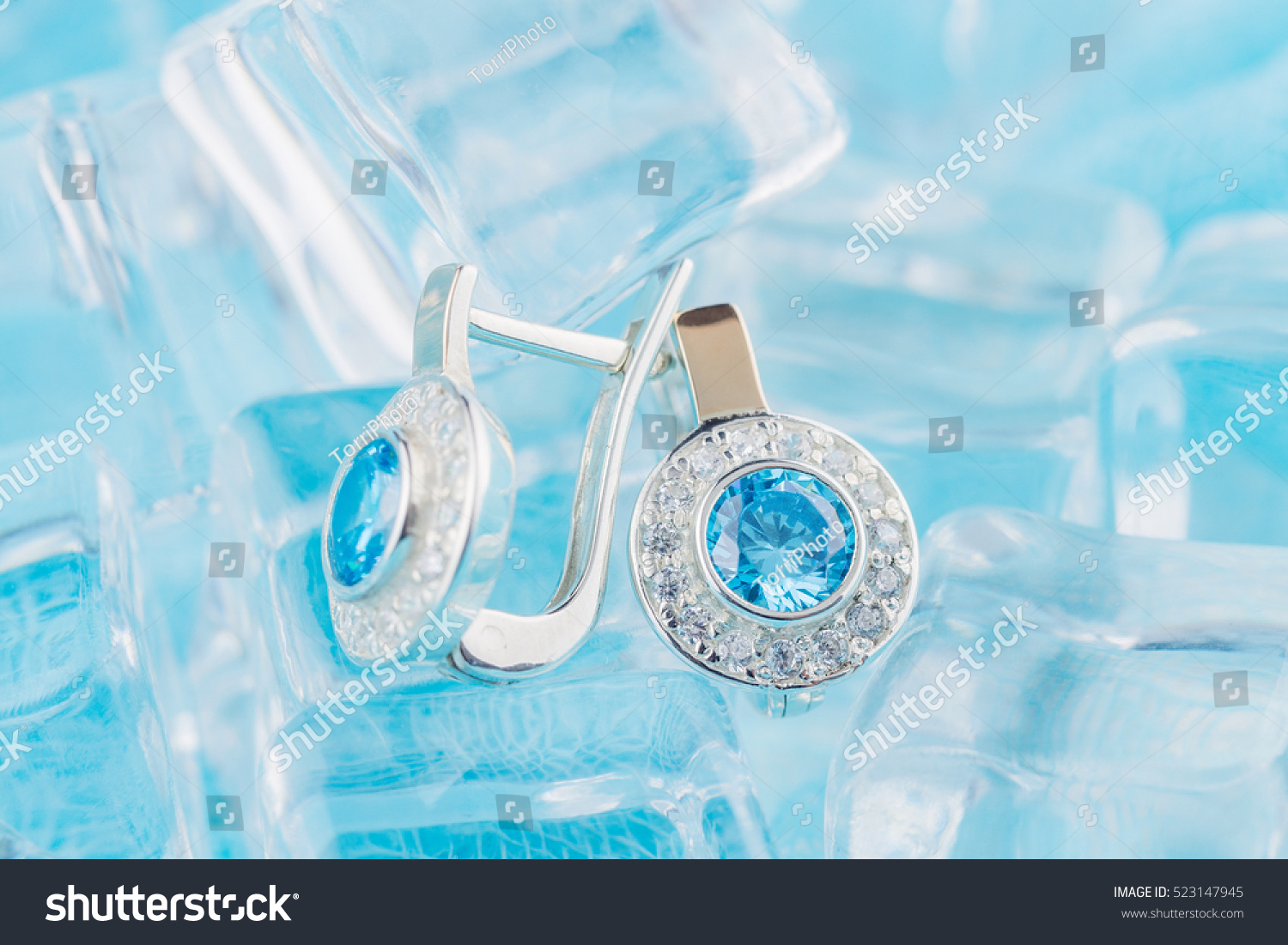 https://www.shutterstock.com/pic-523147945/stock-photo-close-up-earrings-with-zircon-and-expensive-blue-gemstones-still-life-on-ice-blue-background.html