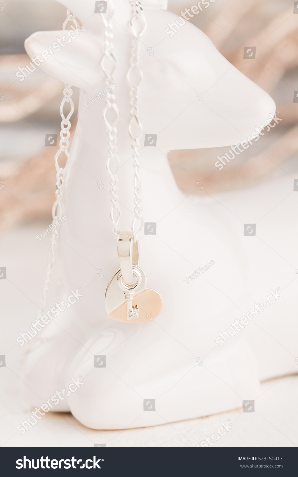 https://www.shutterstock.com/pic-523150417/stock-photo-silver-and-gold-heart-shaped-with-key-pendant-necklace.html