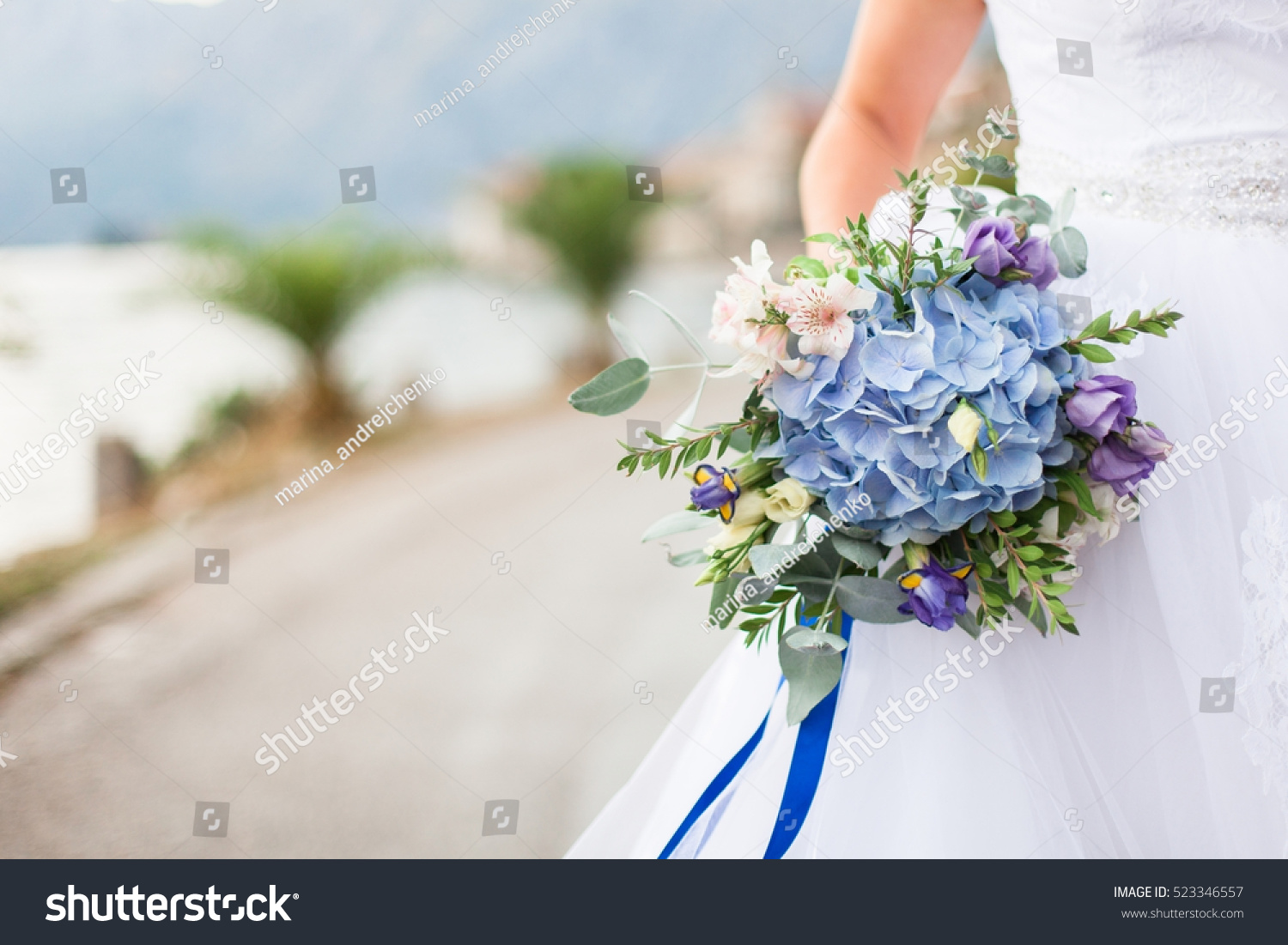 The bride is dressed in white wedding dress and holding wedding id 523346557 izmirmasajfo