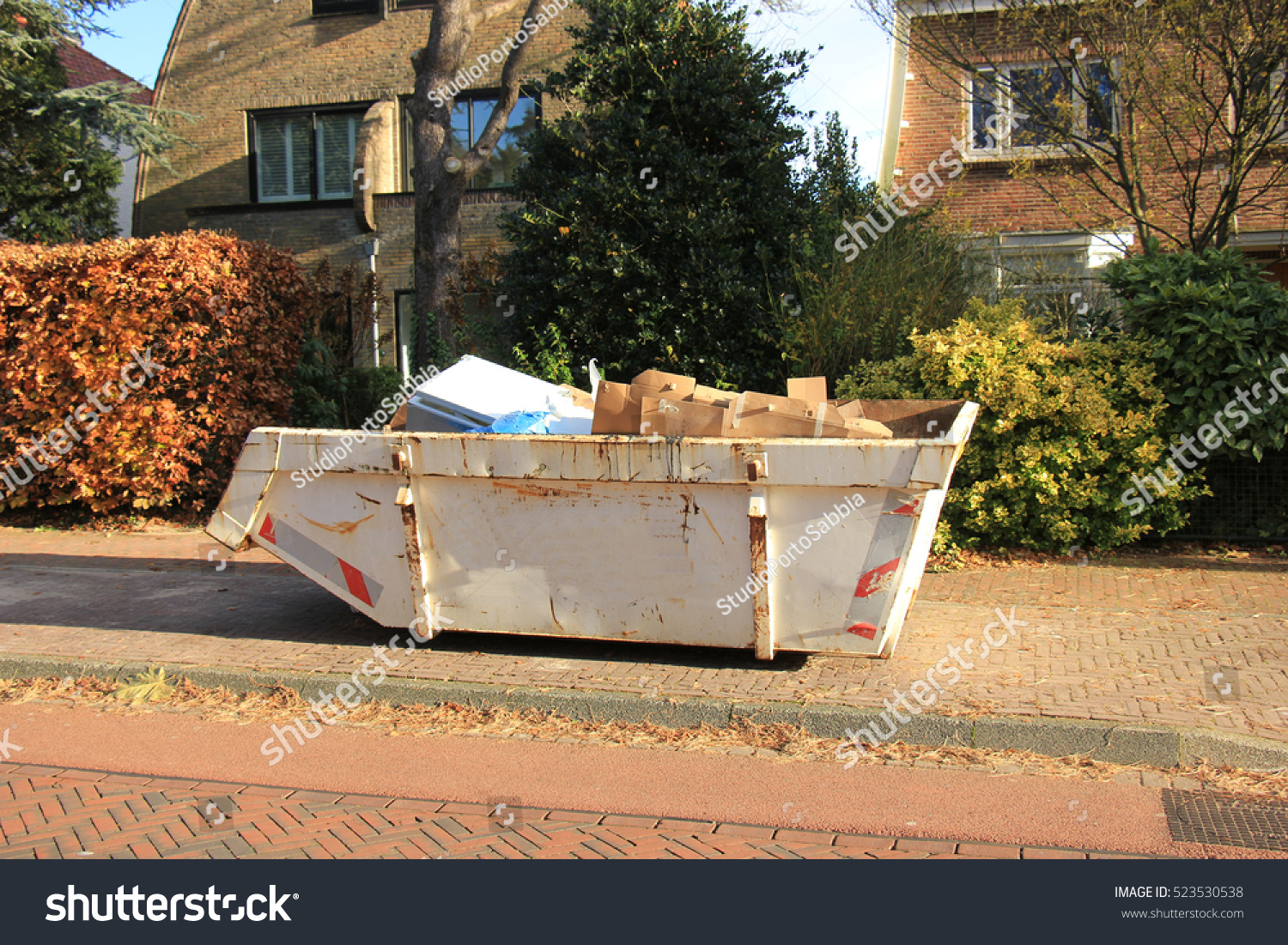 Loaded dumpster near construction site home stock photo for Home renovation builders