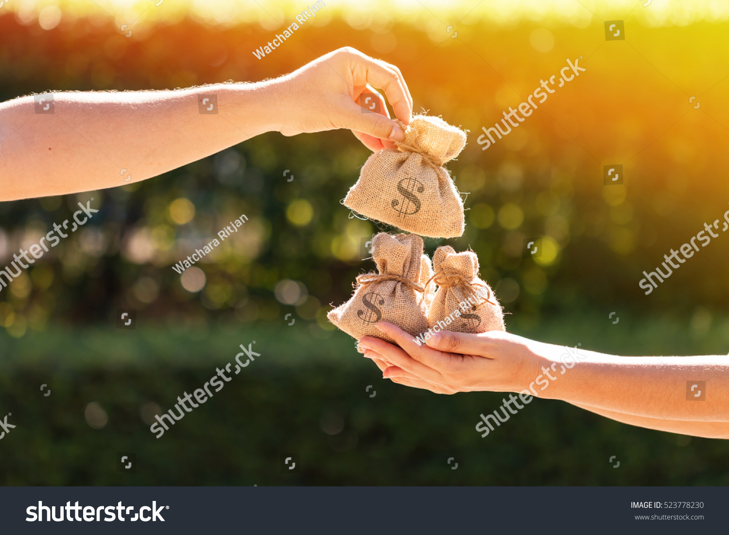 A man and a women hands hold a money bags in the public park for loans to planned investment in the future concept. #523778230
