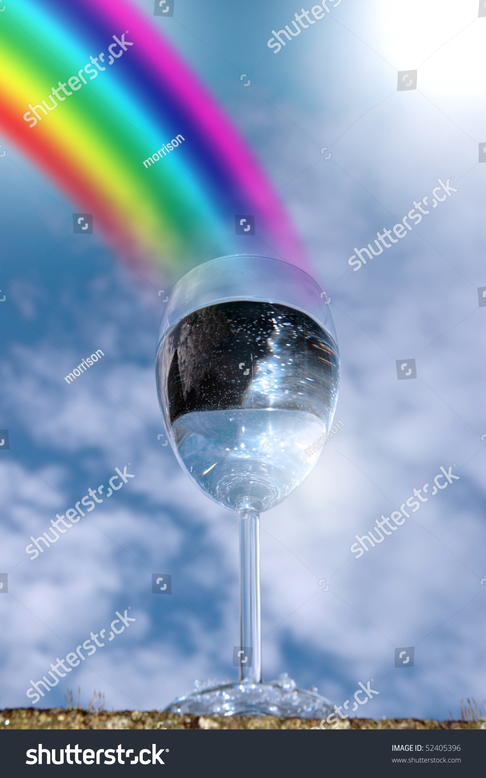 Glass Of Water Against A Sunny Sky With Rainbow Showing