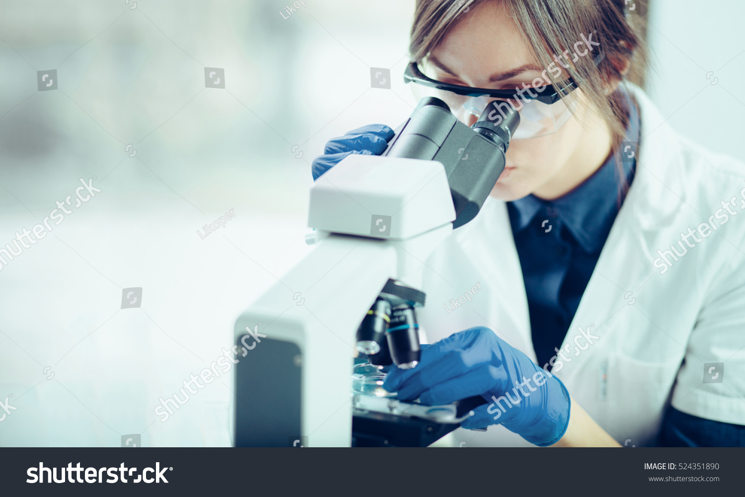 Young scientist looking through a microscope in a laboratory. Young scientist doing some research. #524351890