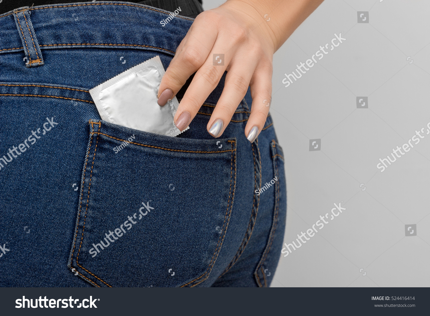 Cropped image of attractive girl in jeans putting a condom into back  pocket, against dark