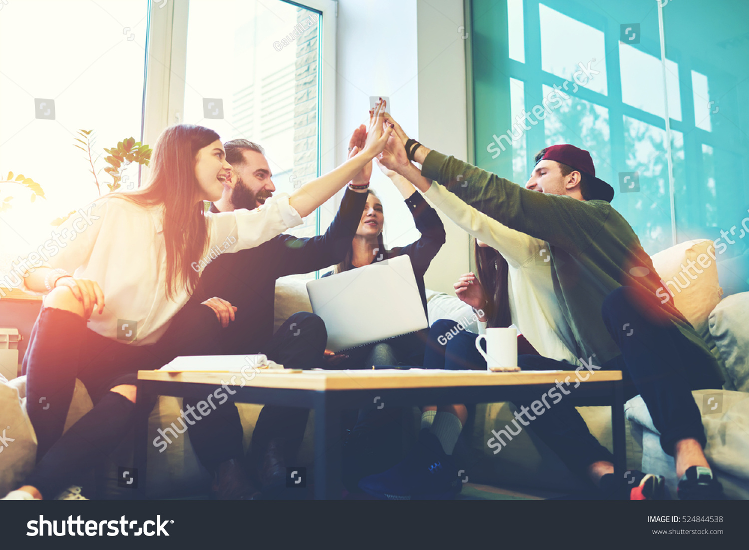Female and male classmates celebrating pathing math examination, feeling exciting and cheerful , giving high five during informal meeting in friendly atmosphere with modern laptop in coworking space #524844538