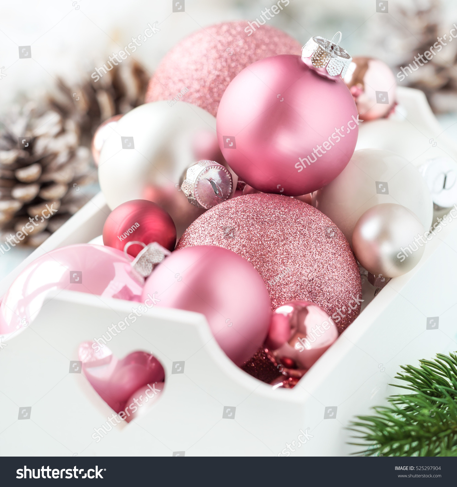 pink christmas baubles in a white shabby chic tray with christmas decorations at the background