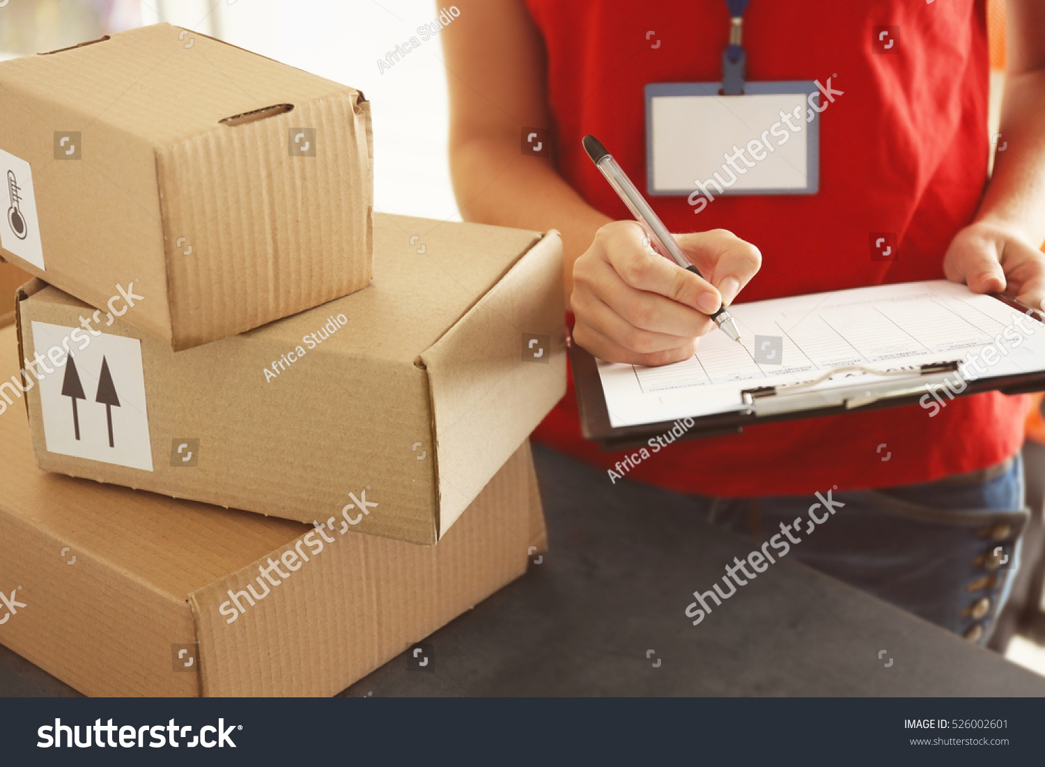 Courier Making Notes In Delivery Receipt At Table Stock Photo ...