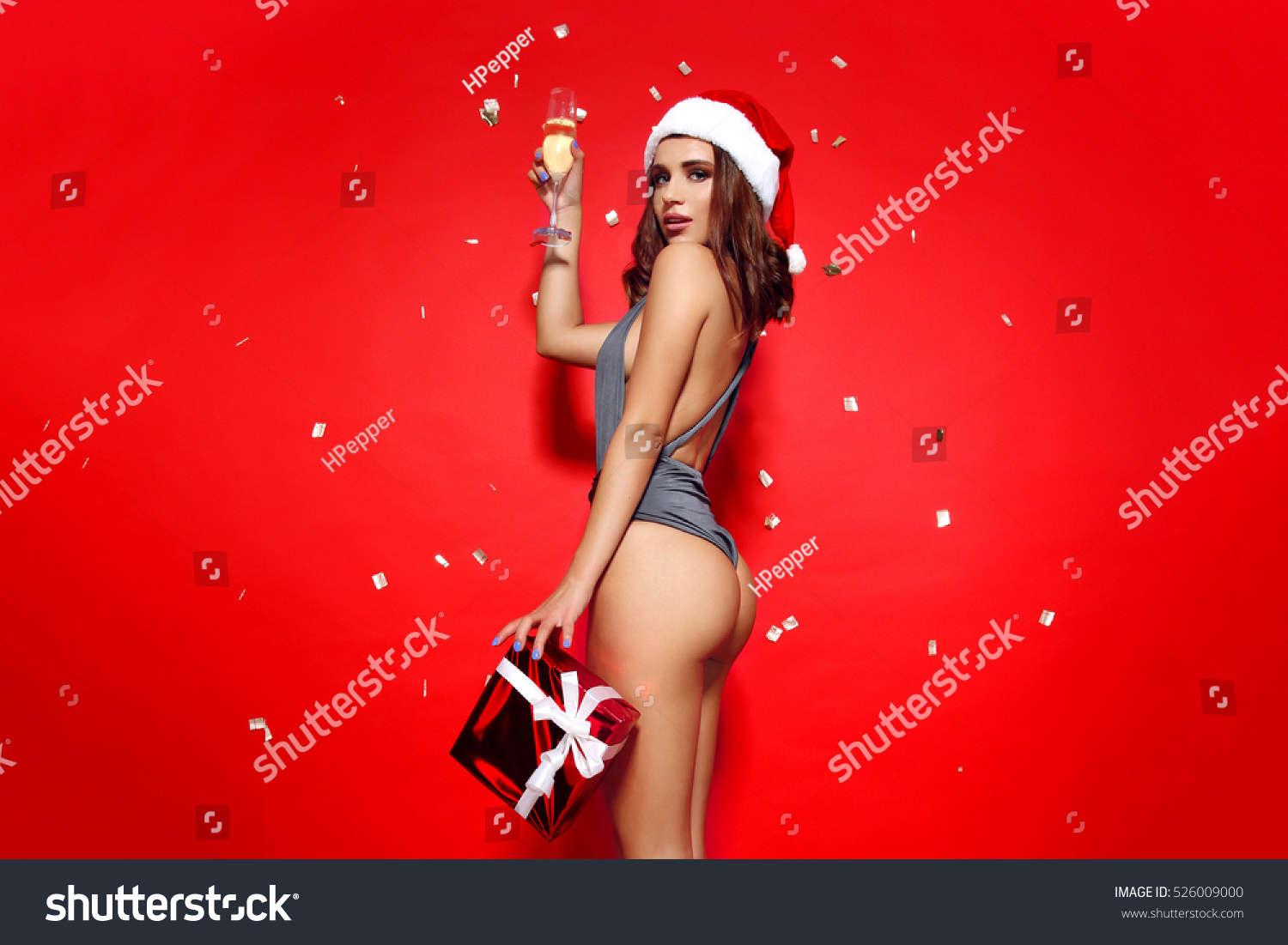 99041fc5d1 beautiful young girl model stands on red background in sexy bathing suit  and a Christmas Santa
