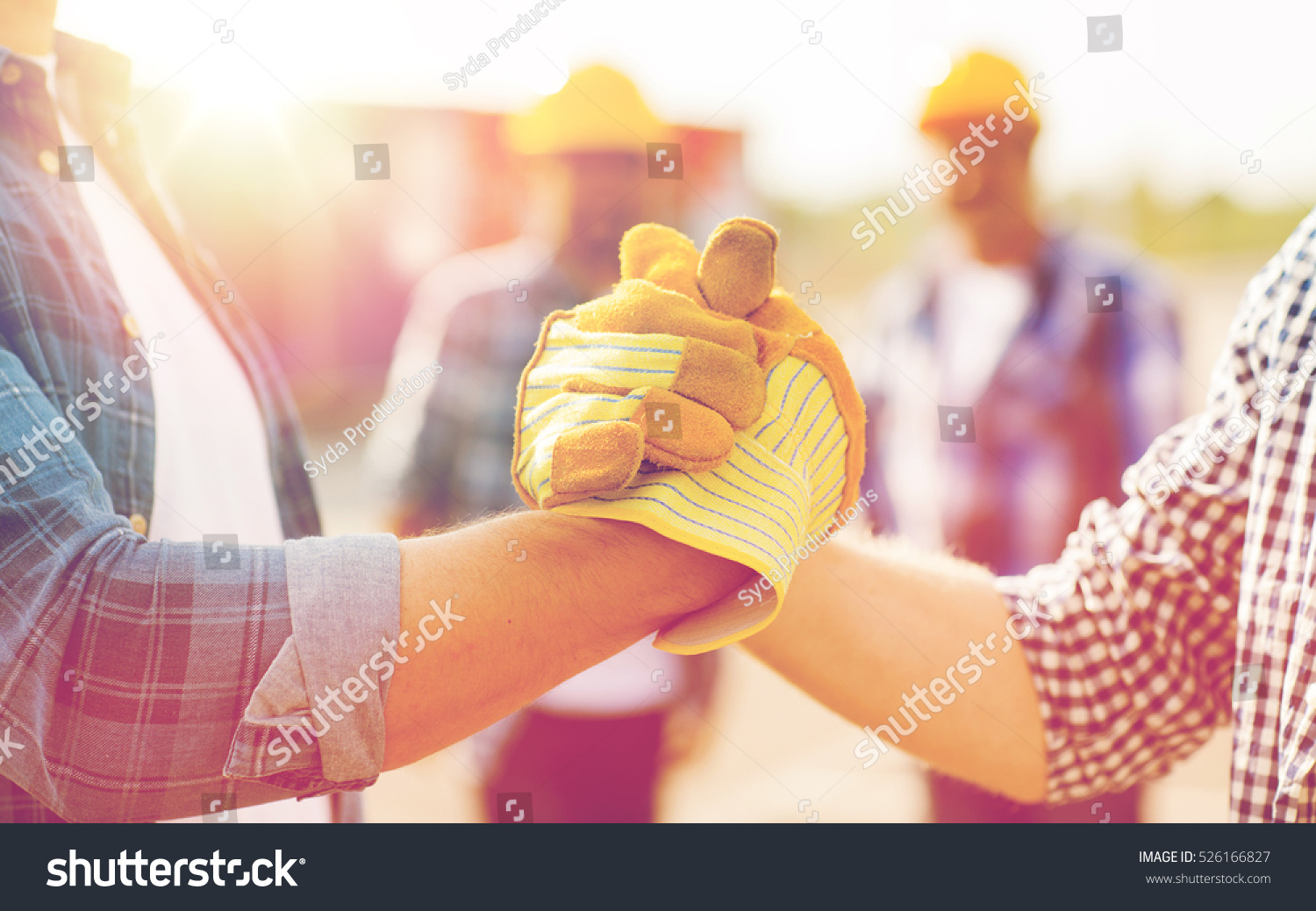 building, teamwork, partnership, gesture and people concept - close up of builders hands in gloves greeting each other with handshake on construction site #526166827