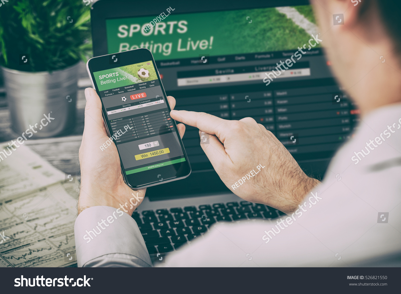betting bet sport phone gamble laptop over shoulder soccer live home website concept - stock image #526821550