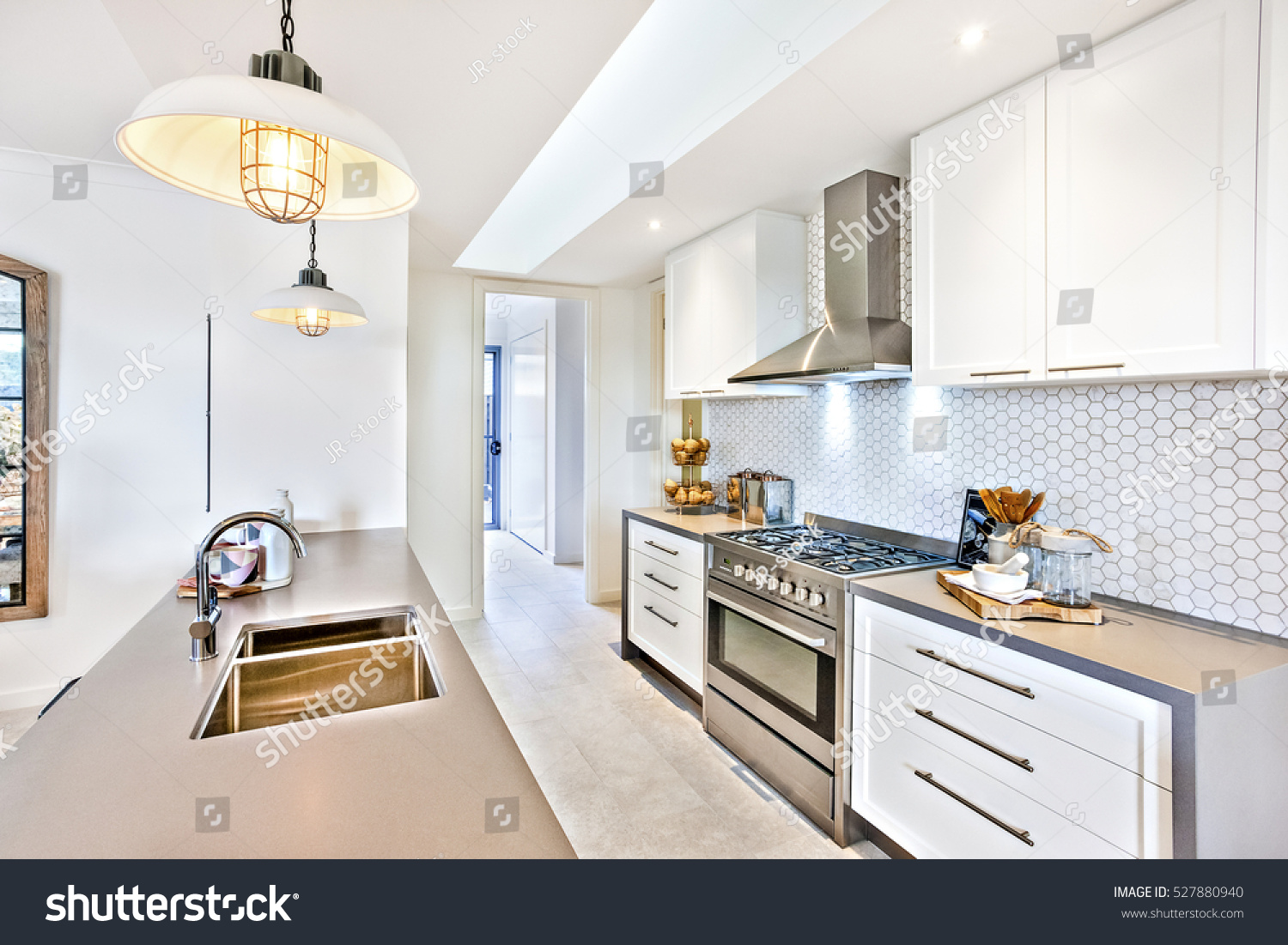 Luxury kitchen with an oven and stove next to pantry cupboards on the wall hanging