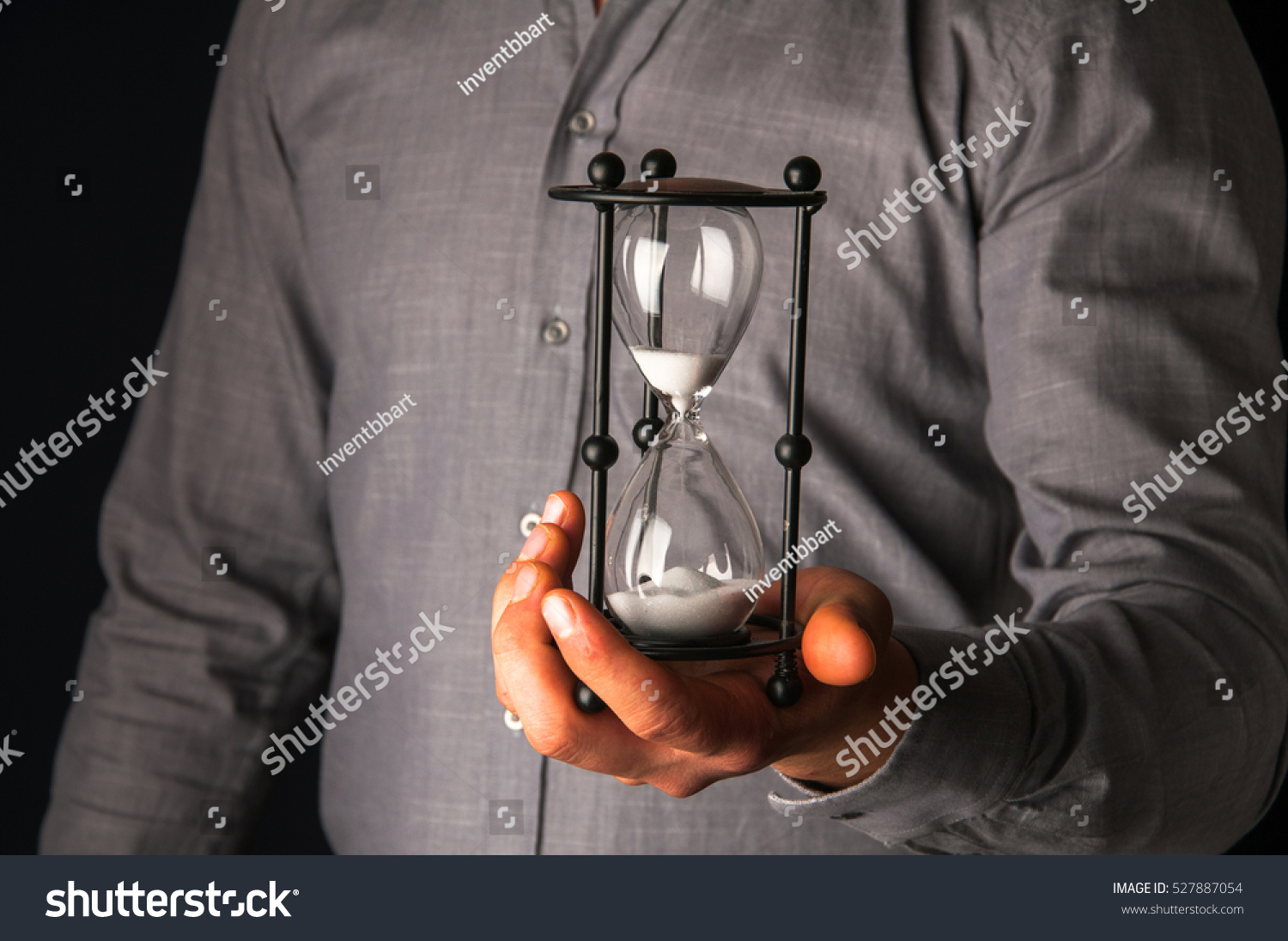 Technology Management Image: Businessman Holding Hourglass In His Hand Stock Photo