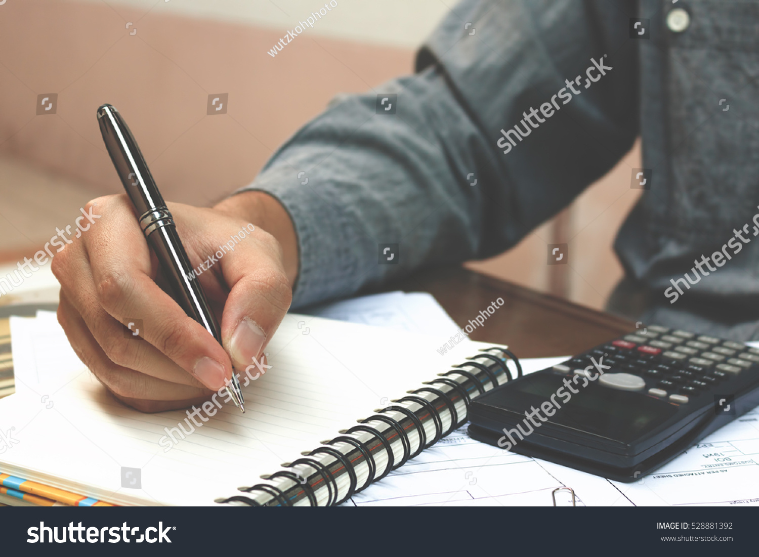 Finance concept Man writing and make note about cost