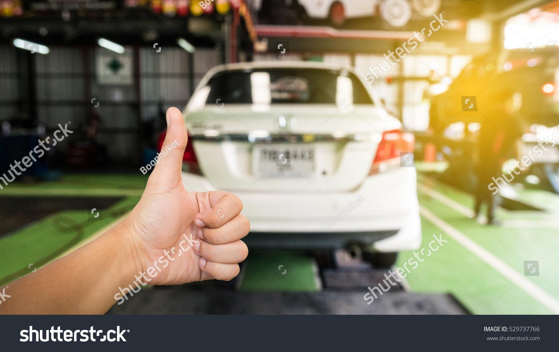 Hands On Garage : Good hand on blur garage background stock photo