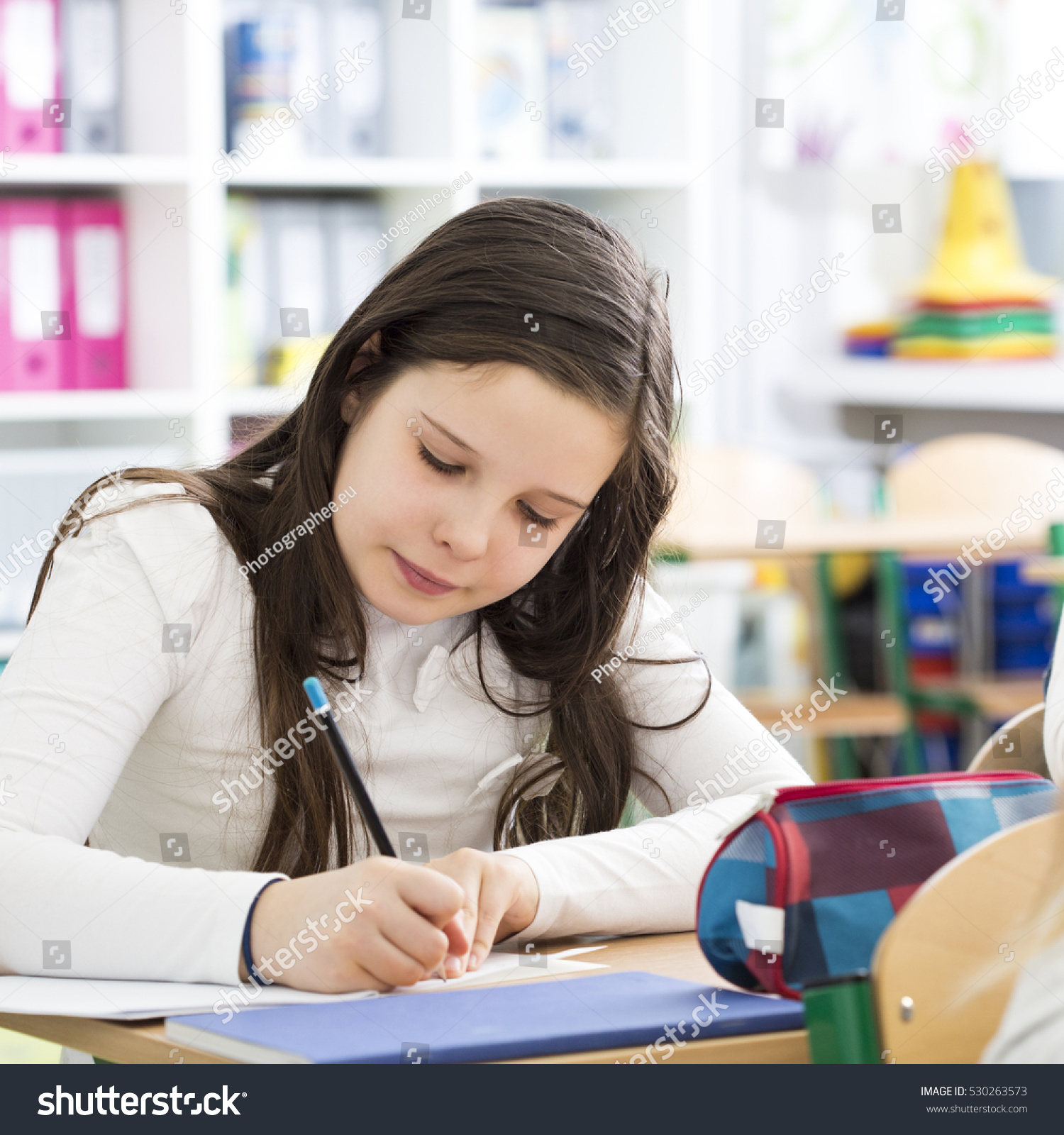 young girl writing essay during lesson stock photo  young girl writing an essay during lesson in primary school