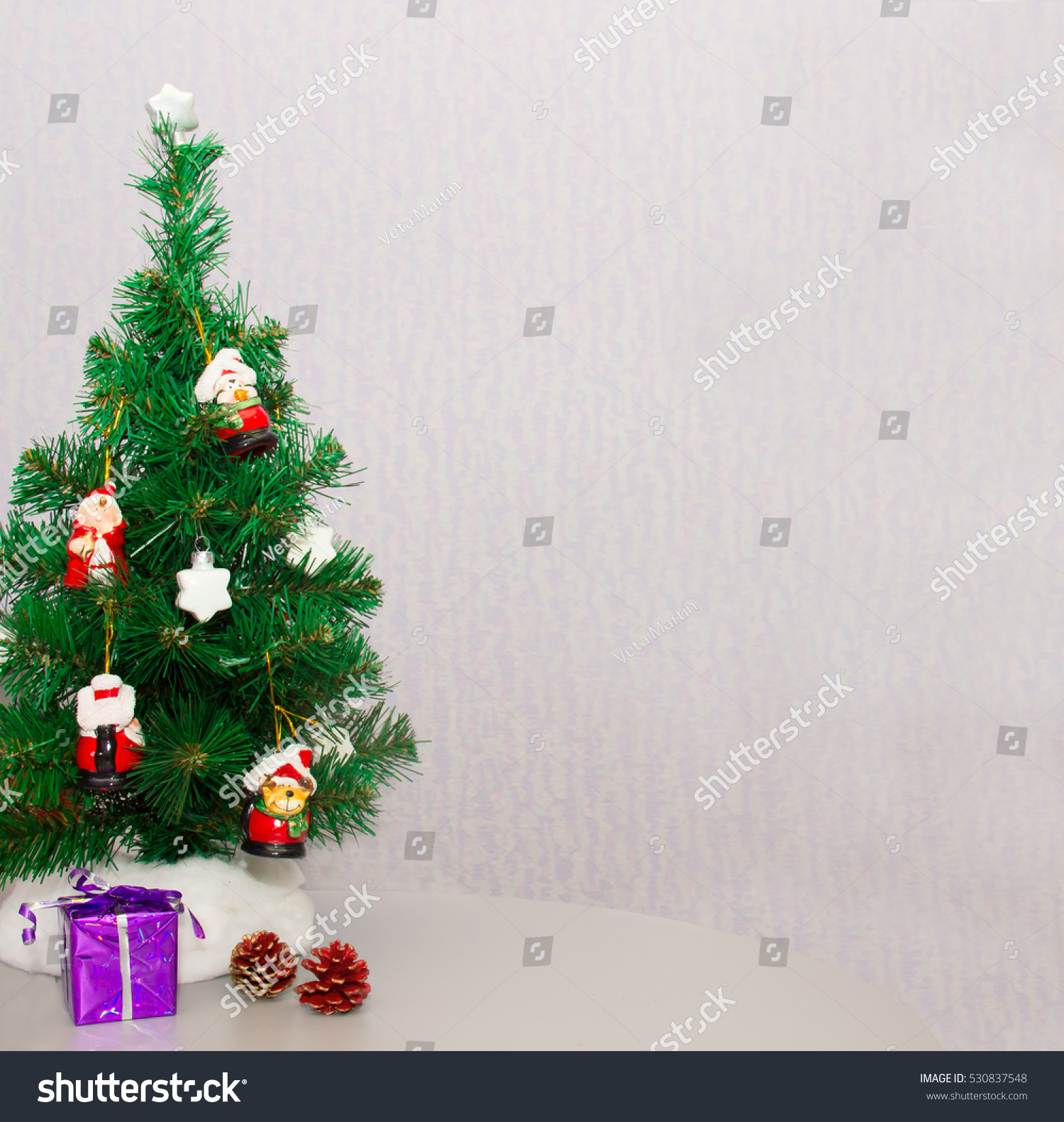 small christmas tree decorated with toys stands on the table with red cones on a bright - Small Purple Christmas Tree