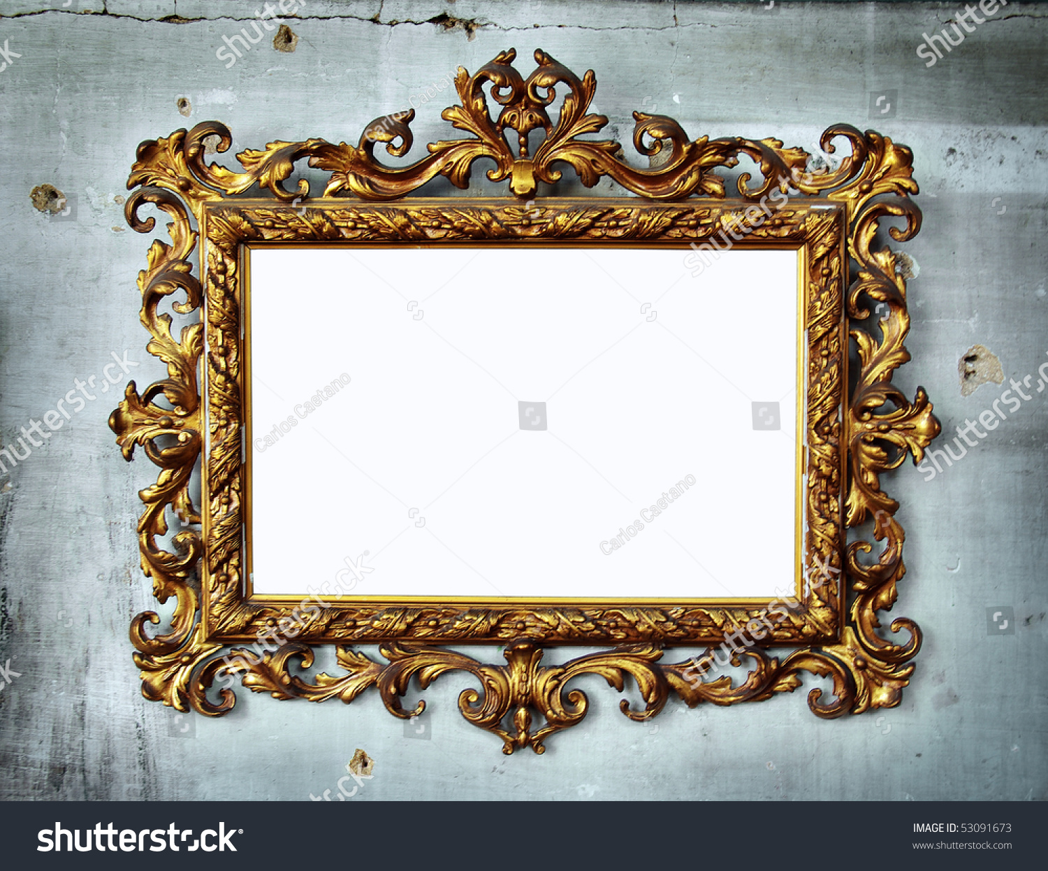 Beautiful golden baroque frame hanged in an old wall with holes and cracks