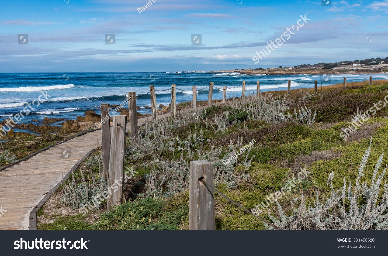 A boardwalk along coastal sand dunes, as waves break along the rocky coastal shores of the Monterey Bay, at Asilomar Beach, in Pacific Grove, along the central coast of California.