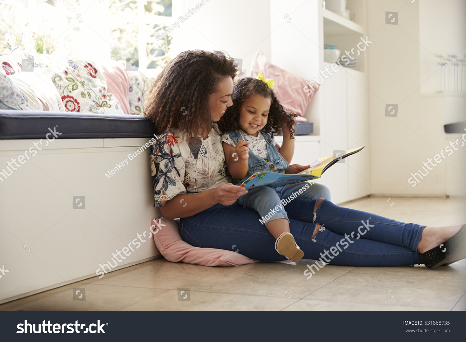 mother sitting on floor reading book stock photo 531868735 shutterstock. Black Bedroom Furniture Sets. Home Design Ideas