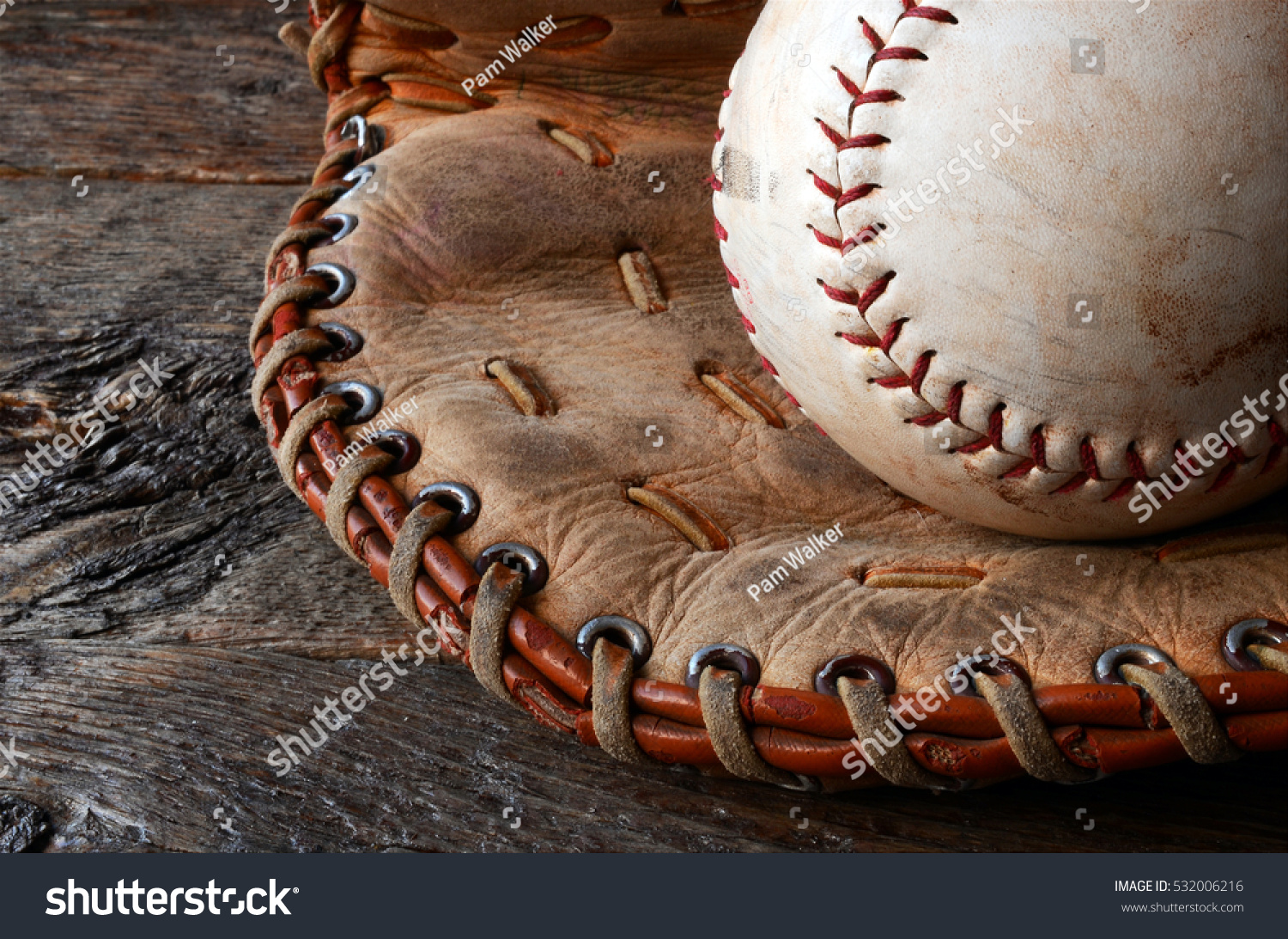 A low angle image of an old used baseball and leather baseball glove. #532006216