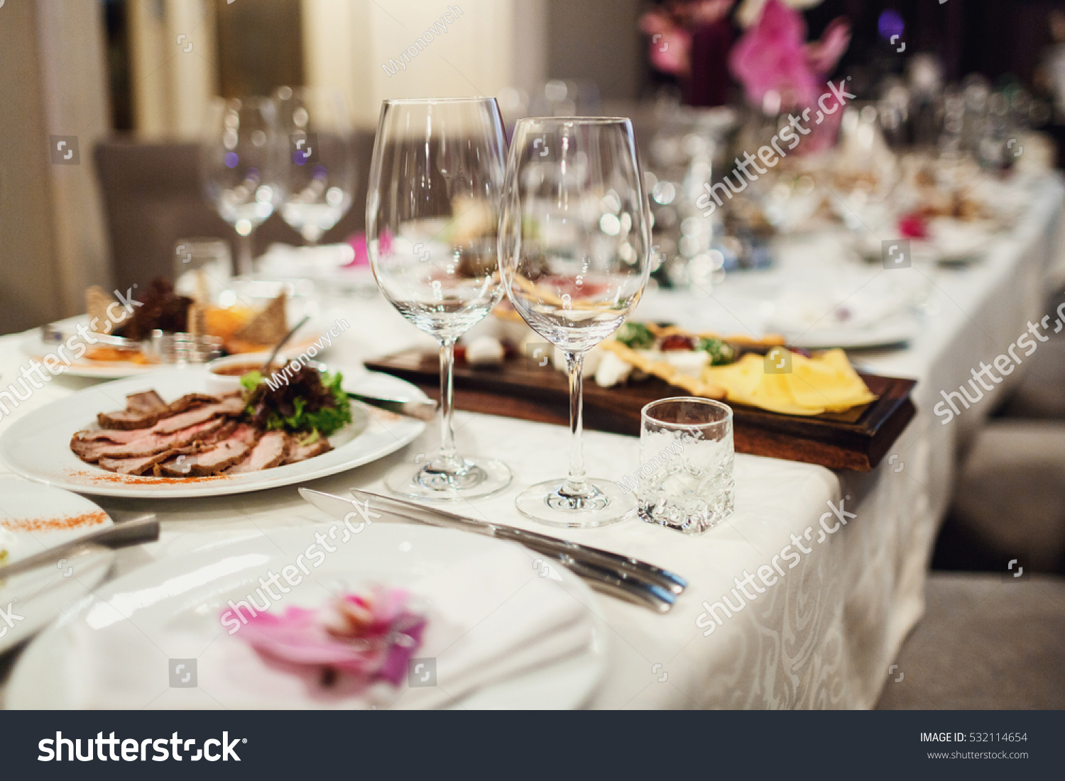 Sparkling Glasses Stand On Dinner Table Before Tray With Meat