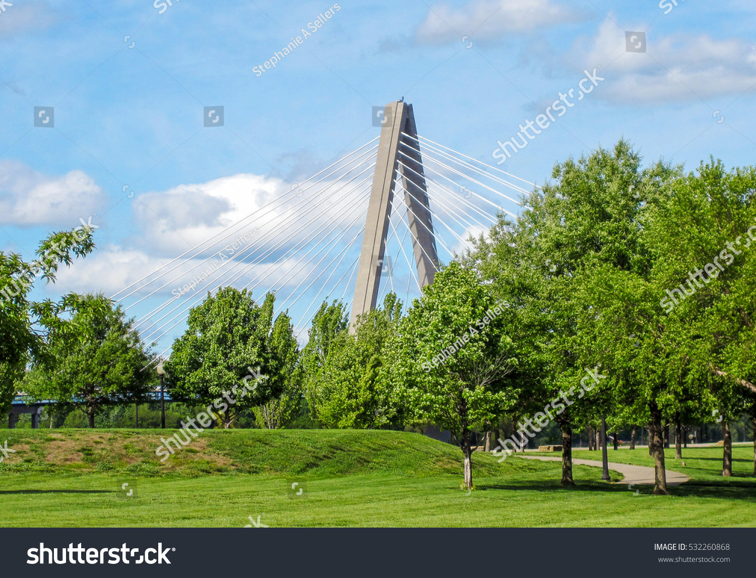A view of the Christopher S Bond Bridge over the Missouri River hiding behind trees