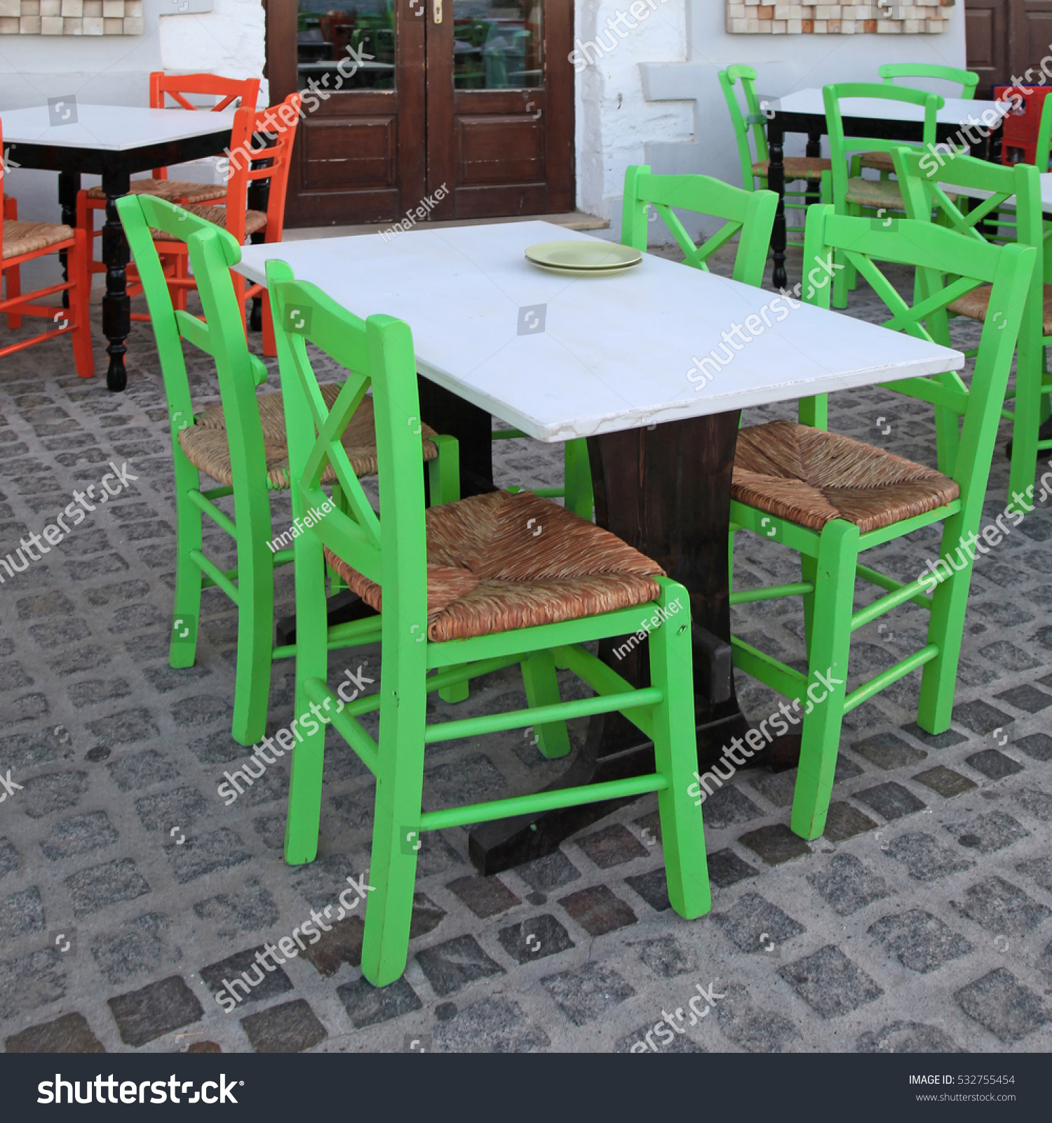 Greek outdoor cafe with green wooden chairs crete greece square image