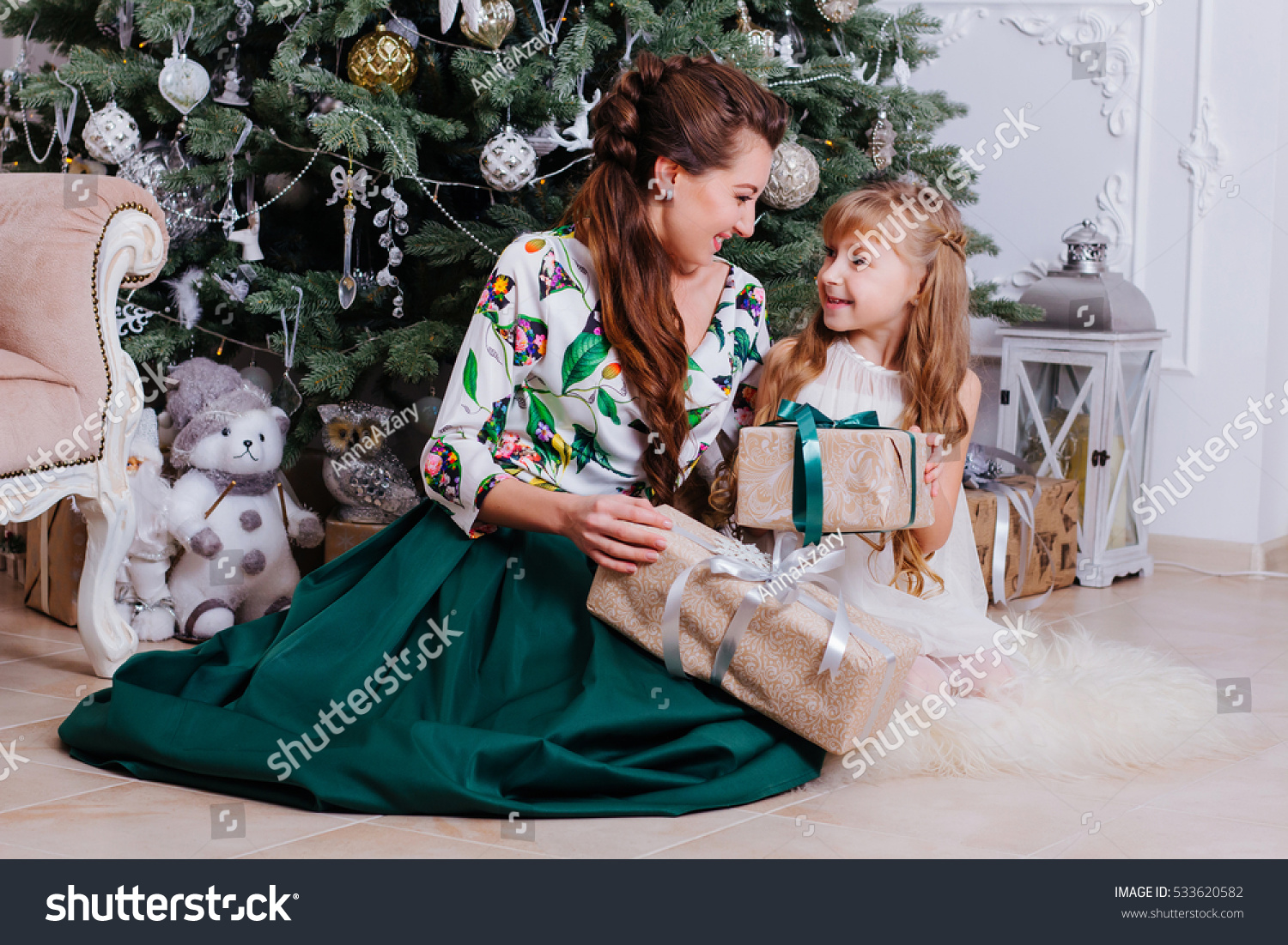 S woman in party dress decorating indoor christmas tree