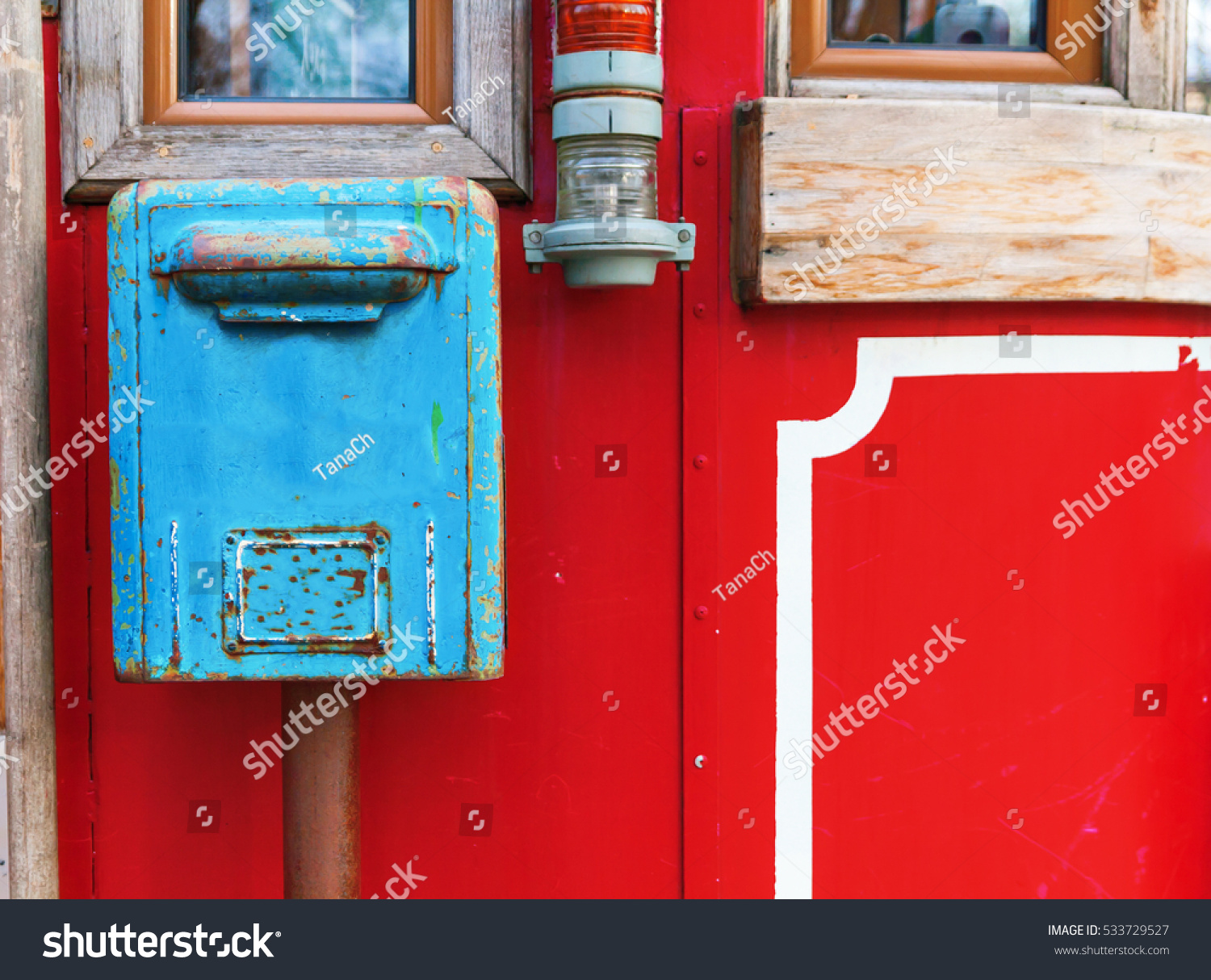 Old Blue Mailbox Hanging On Red Wall.